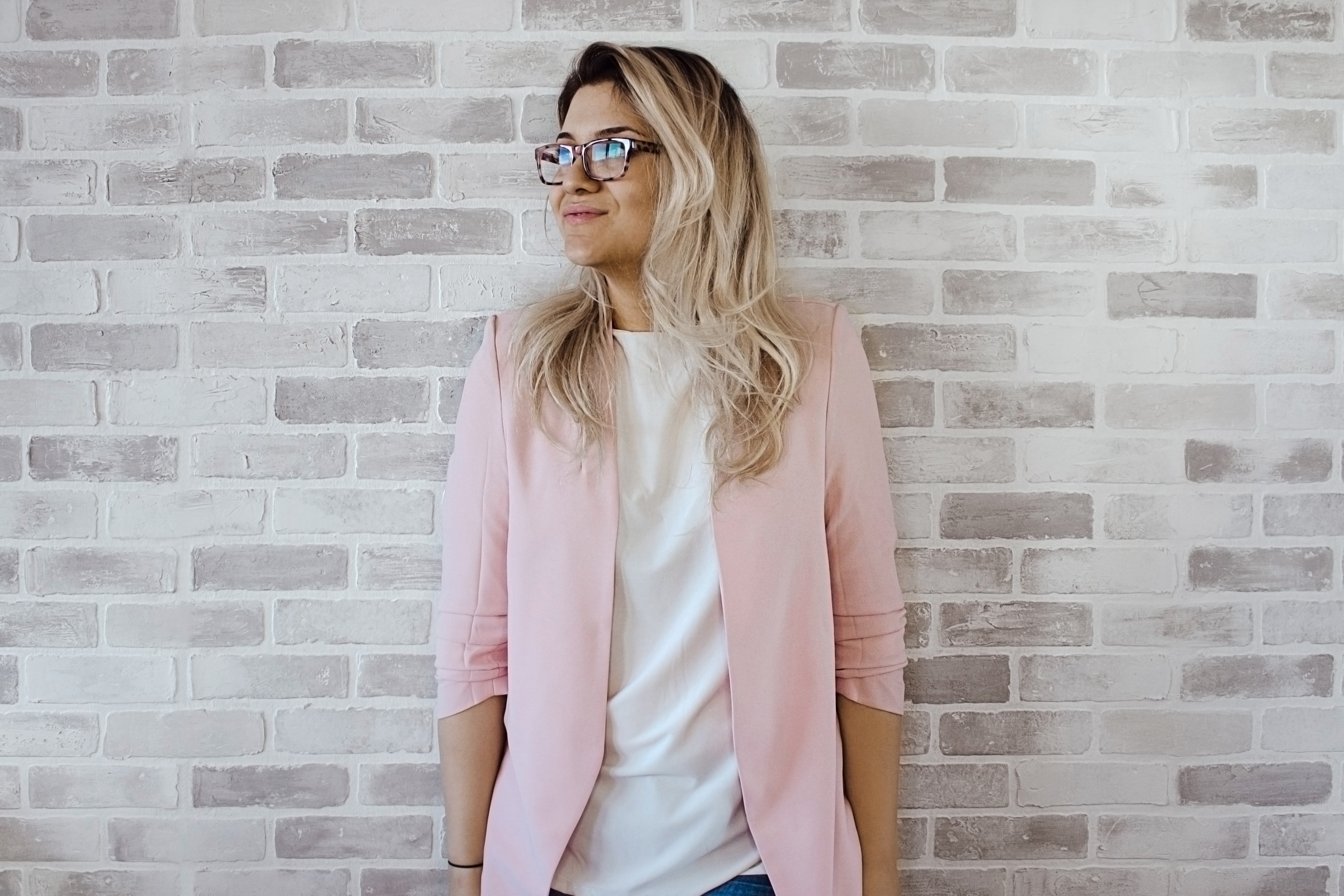 Woman in pink cardigan and white shirt leaning on the wall photo