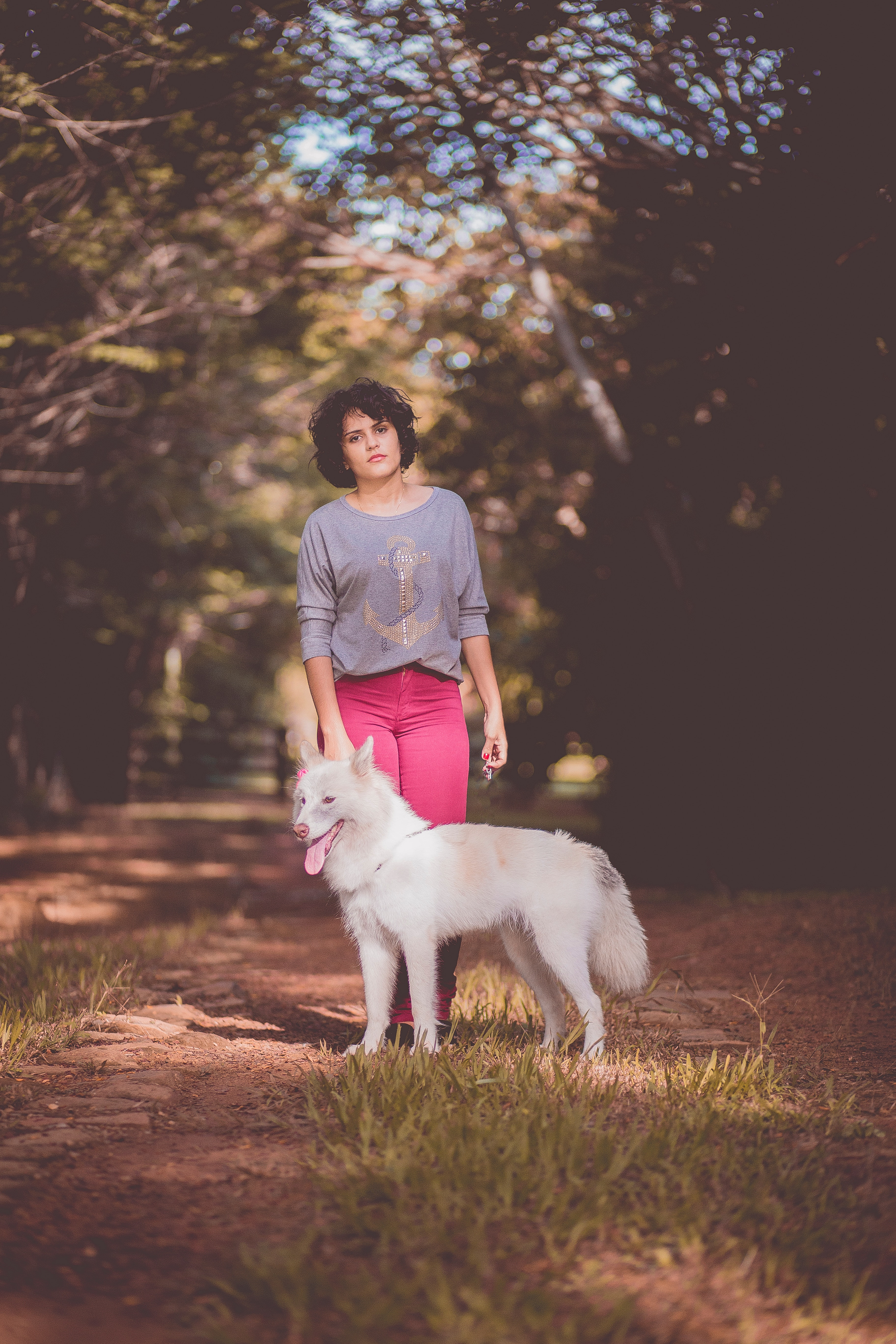 Woman in purple long sleeve shirt and pink jeans standing next to white german spitz with background of green trees during day photo