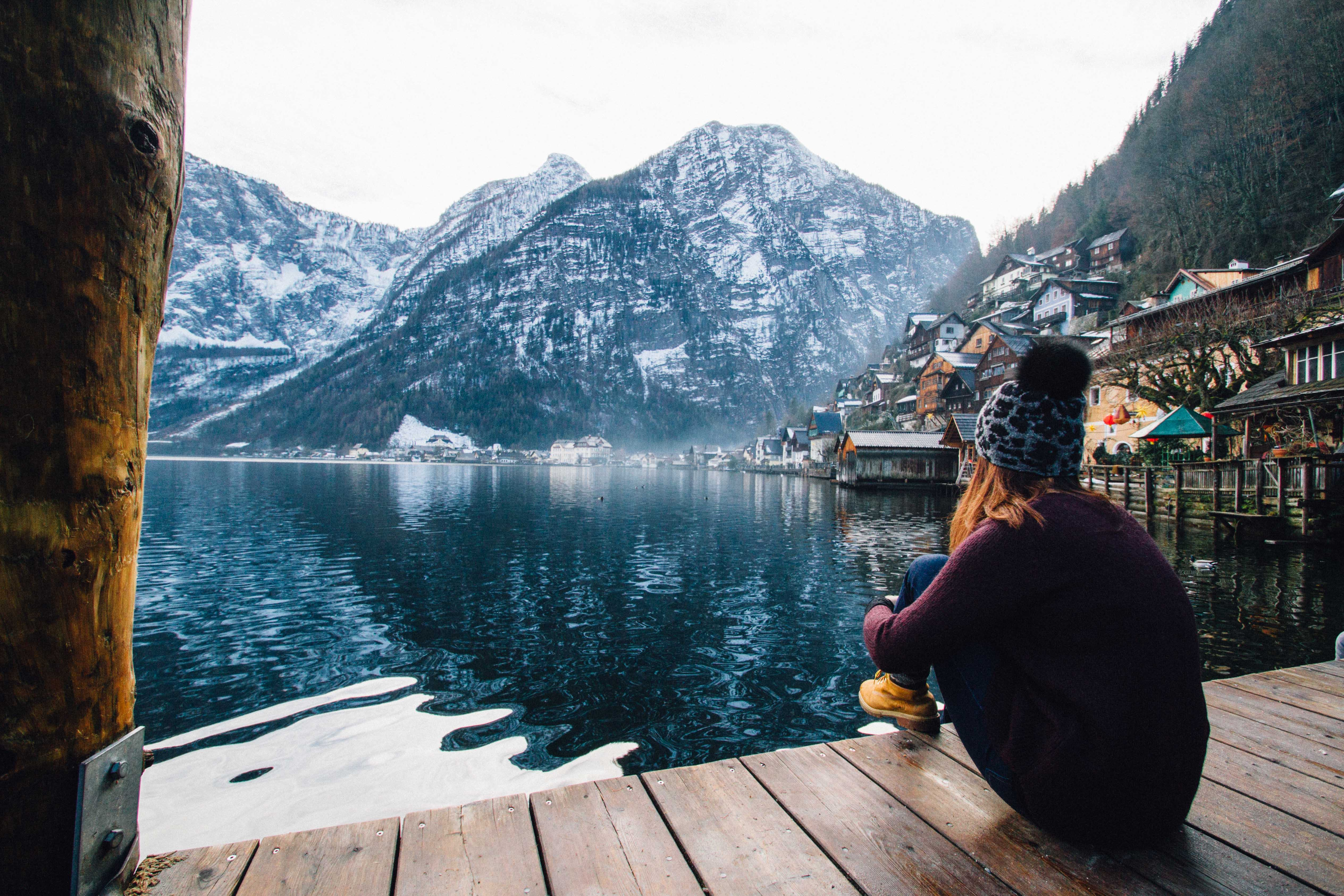 Woman in purple sweater sitting on wooden floor with view of lake and mountains photo