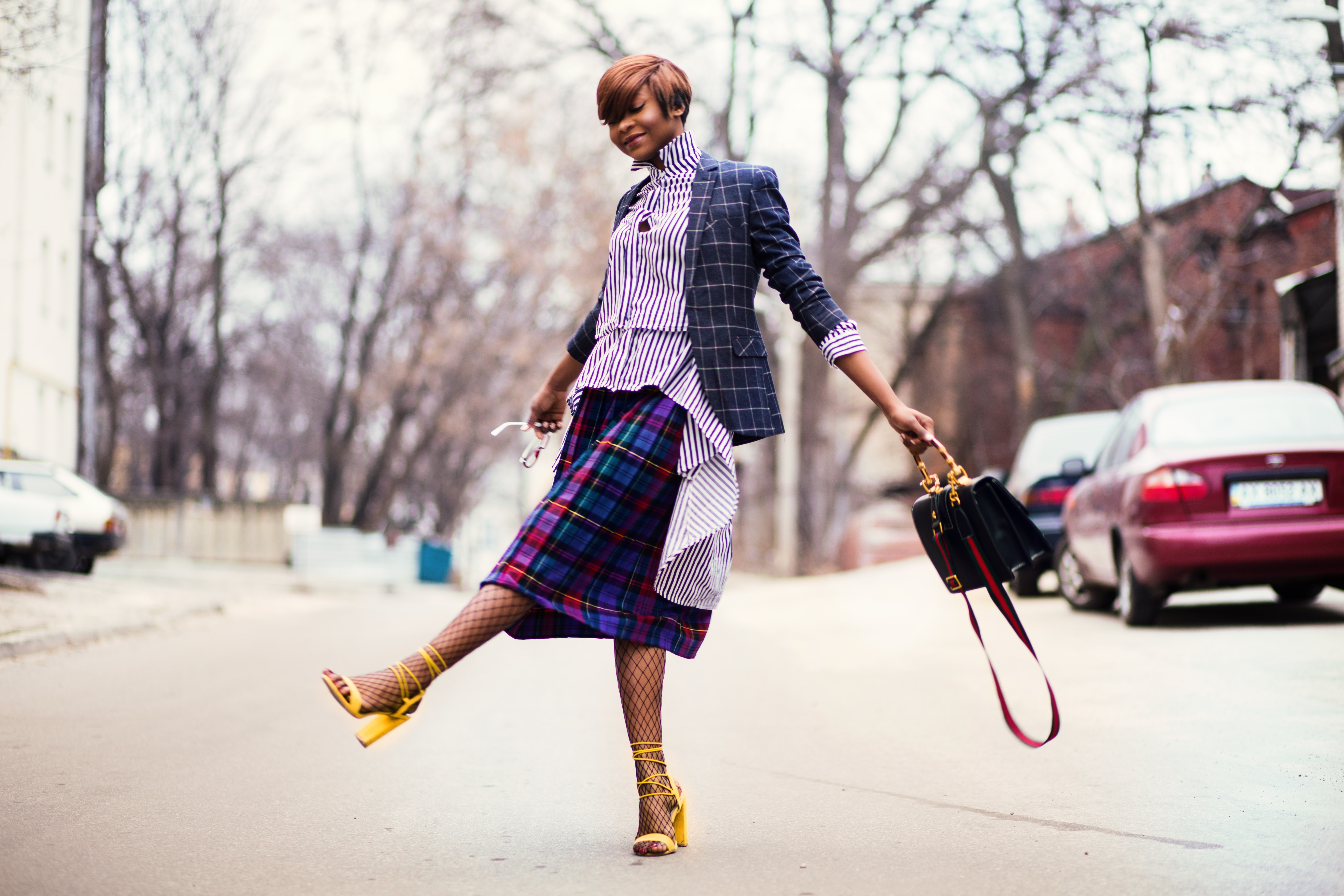 Woman in purple top and plaid skirt near car photo