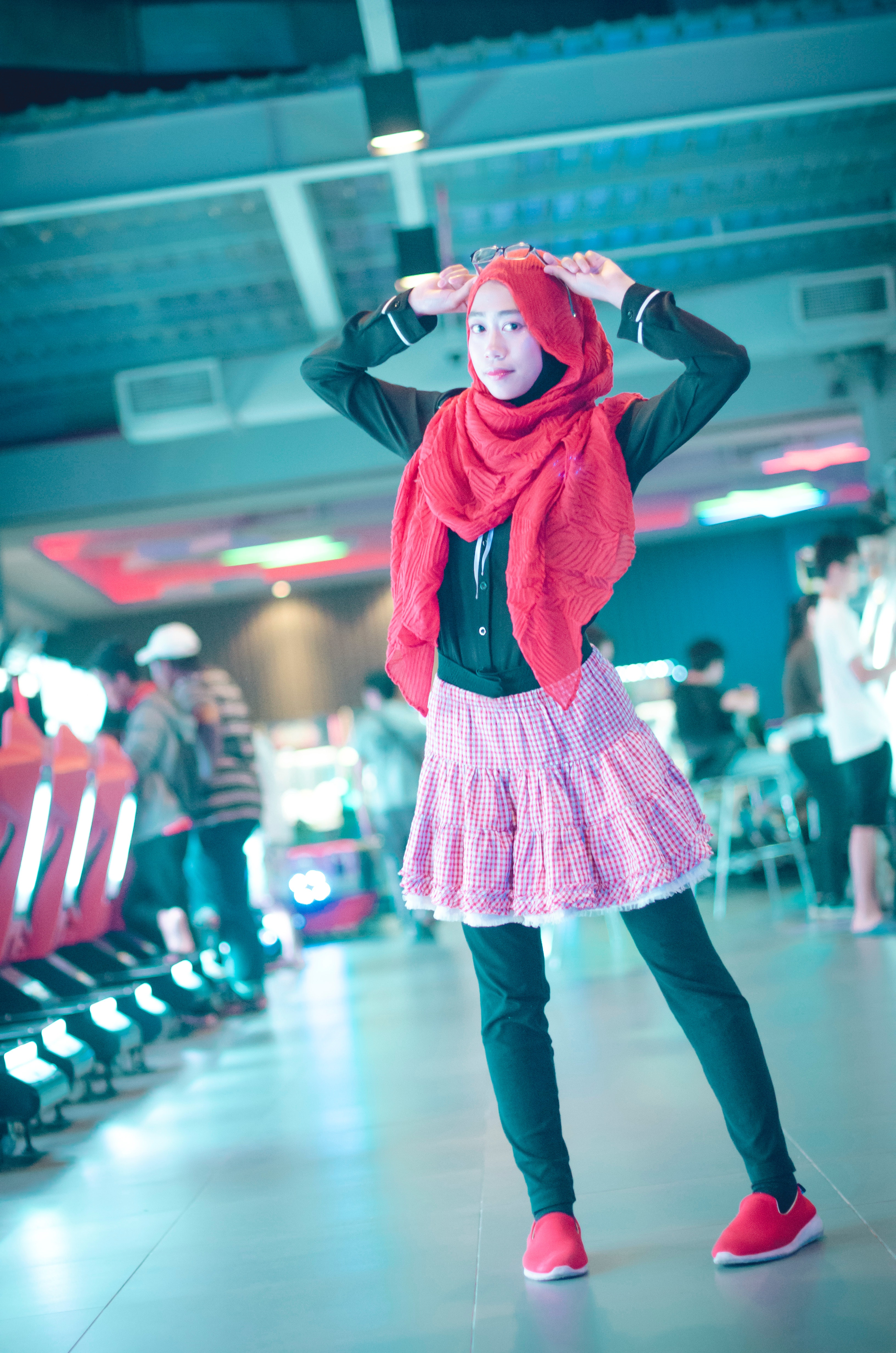 Woman in red head scarf with black dress shirt and pink skirt photo