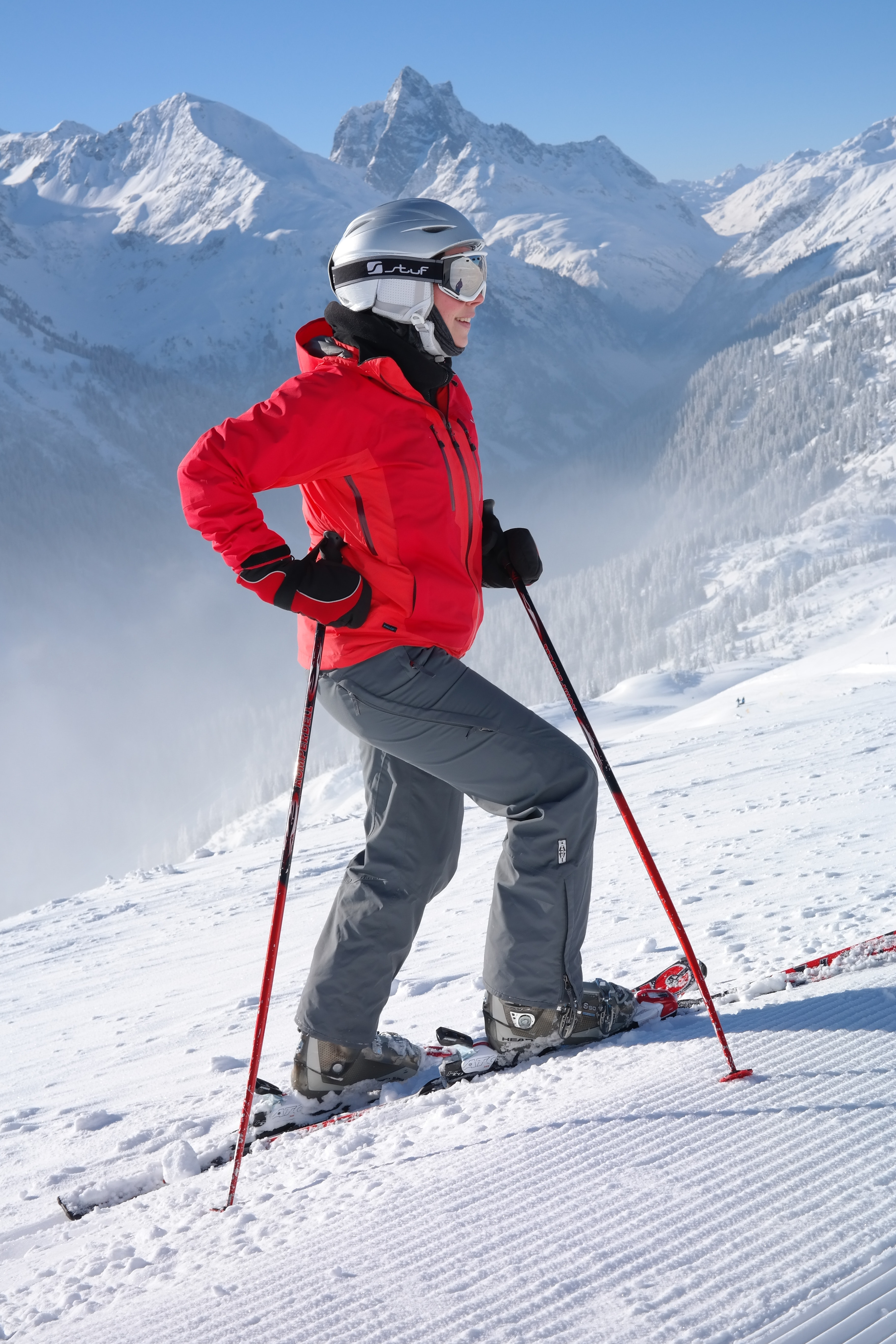 Woman in red jacket wearing helmet and holding snow ski stick photo