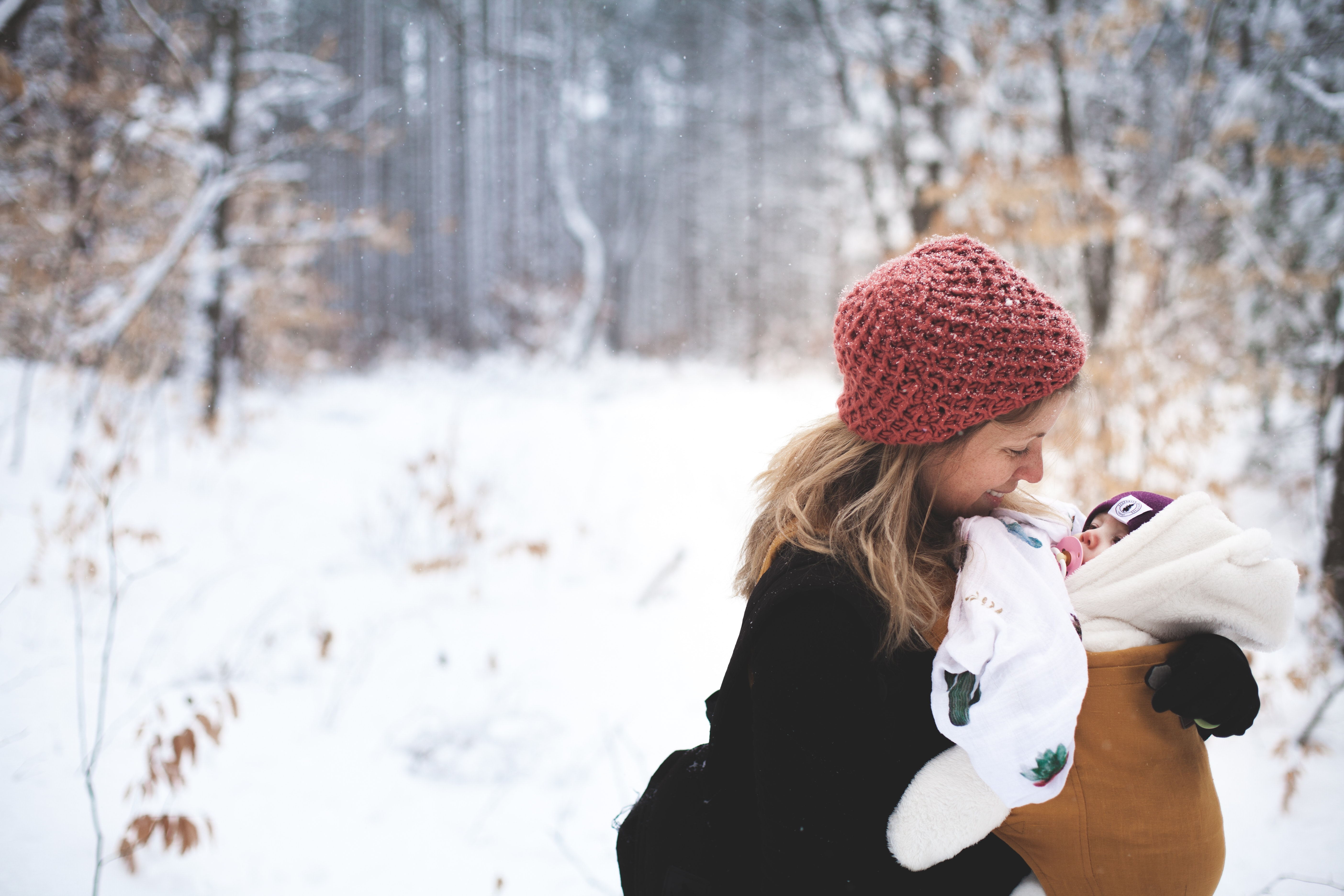 Woman in red knitted cap and black top holding baby with brown carrier photo