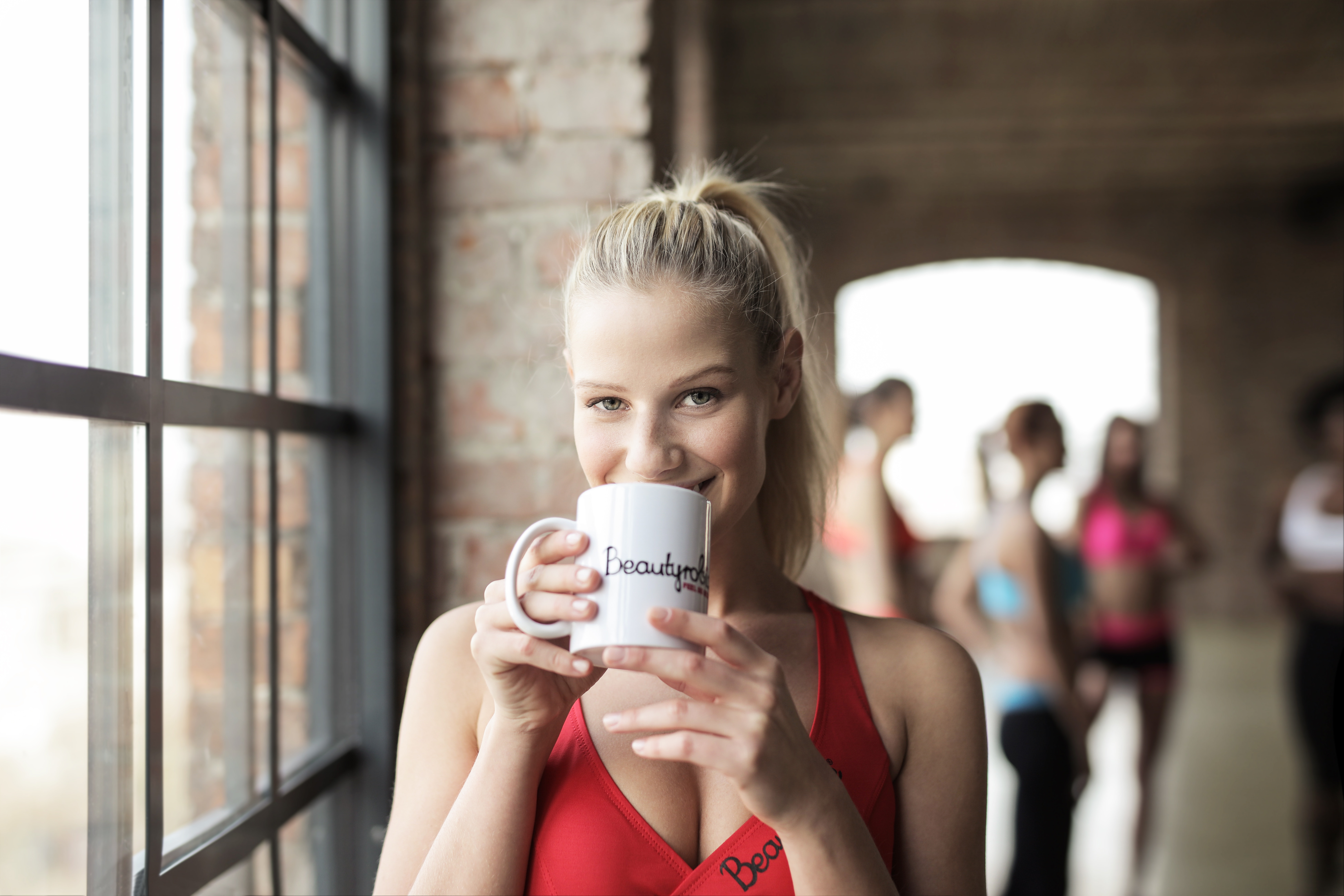 Woman in red scoop-neck tank top holding white mug photo