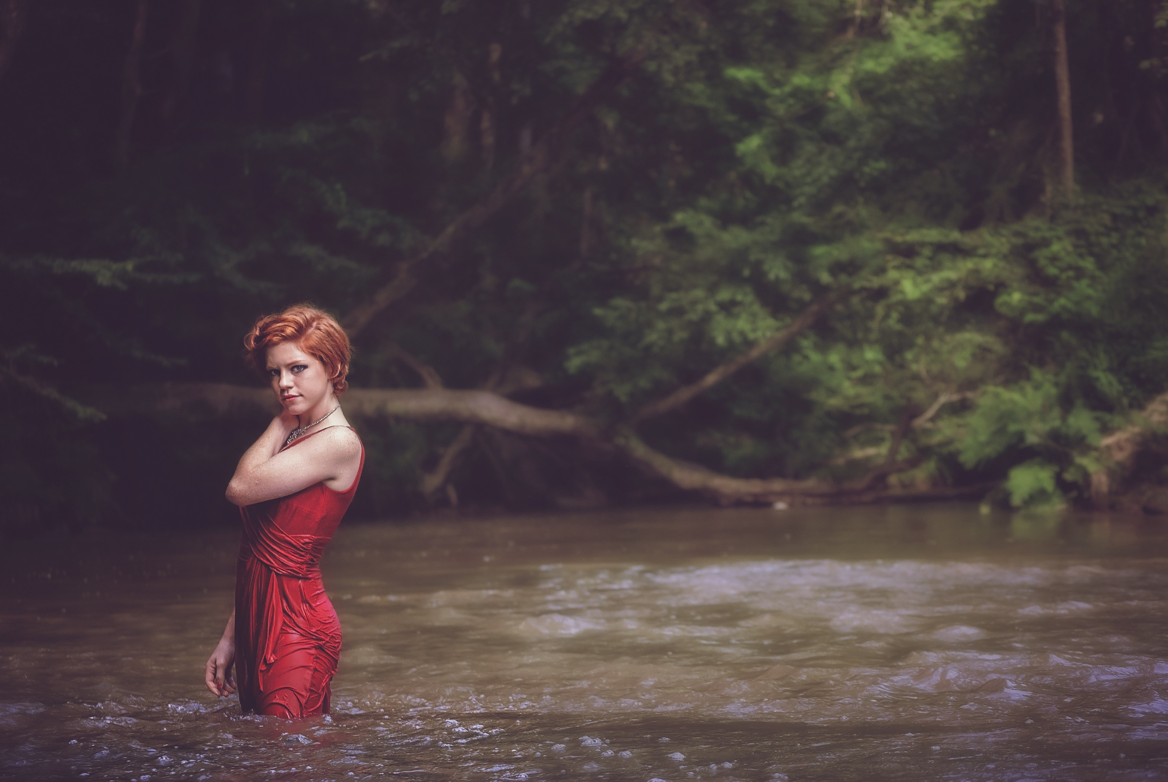 Woman in red string spaghetti strap dress on body of water near forest photo