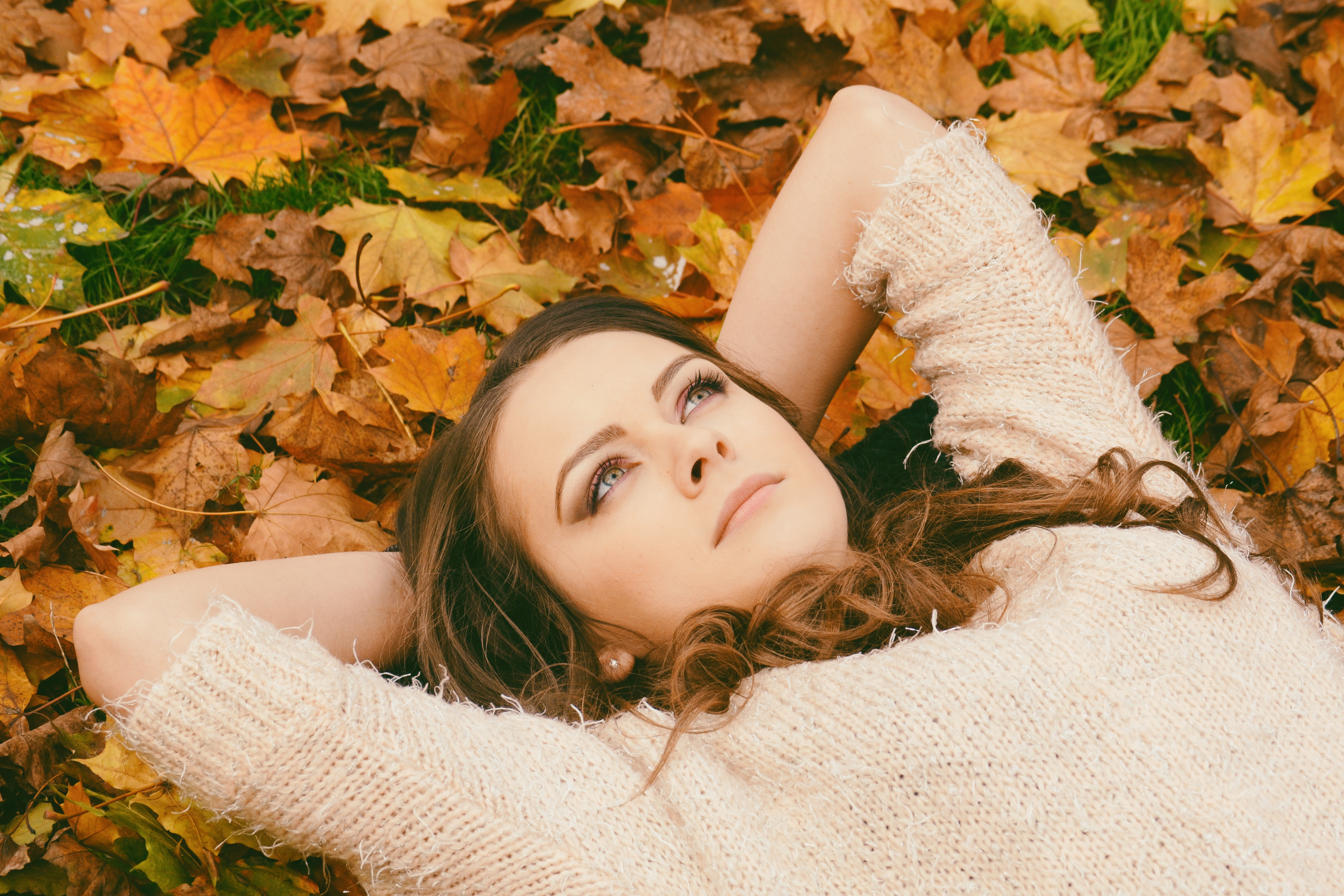 Woman in sweater laying on dried maple leaves photo