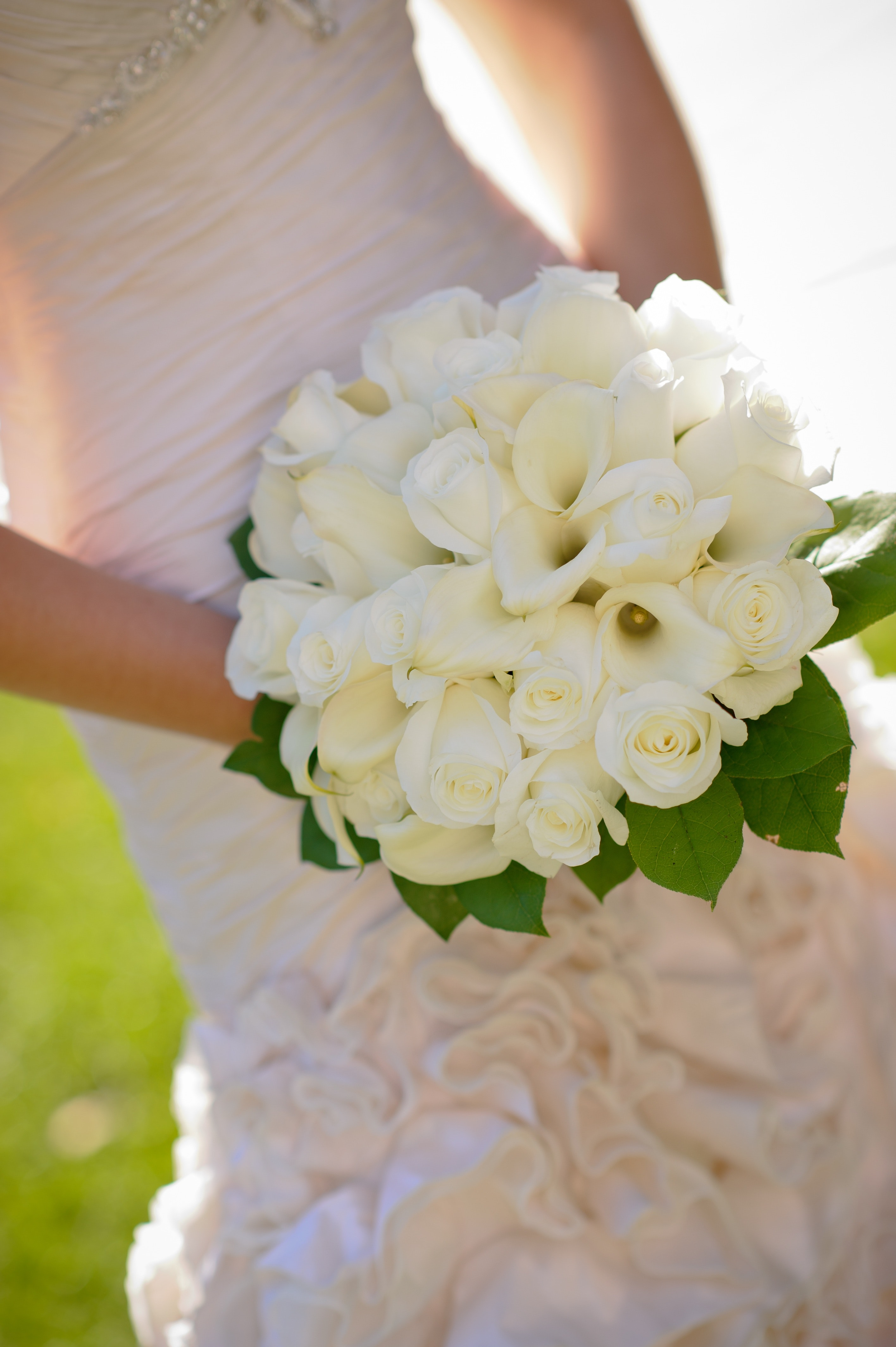 Woman in wedding dress holding white flower bouquet photo