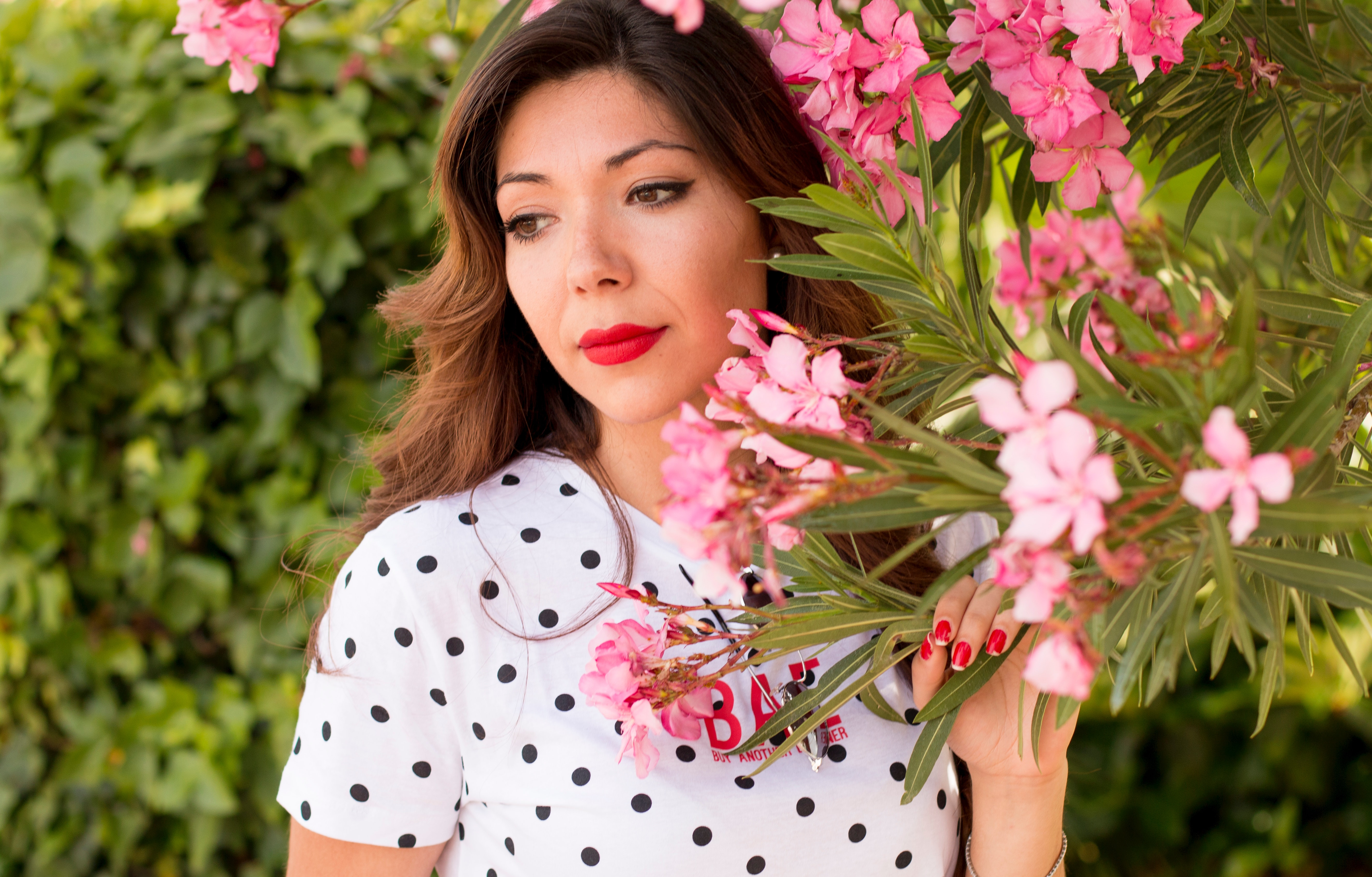 Woman in white and black polka dots dress near pink flowers during daylight photo