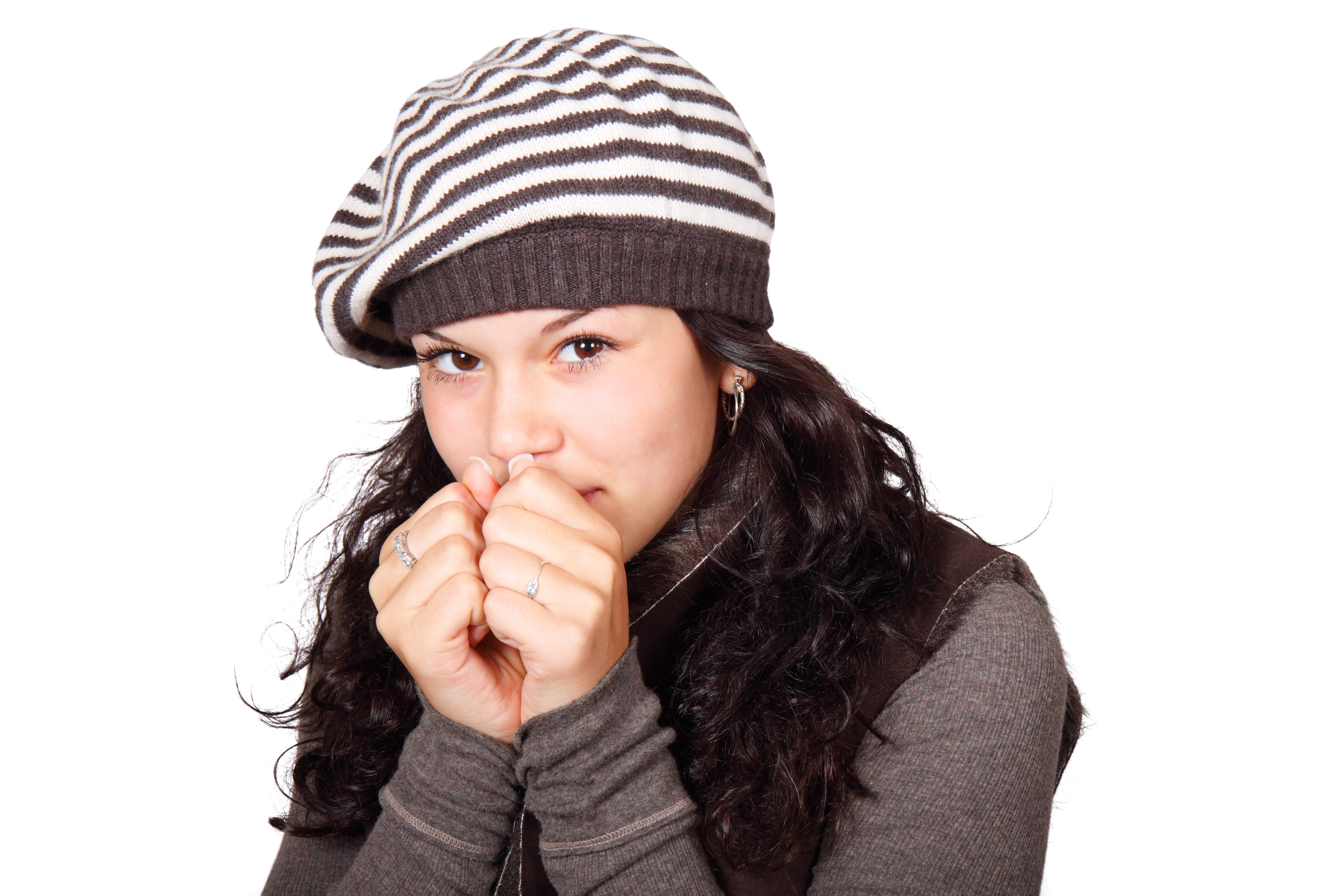 Woman in white and black stripe cap and grey shirt hands to face photo