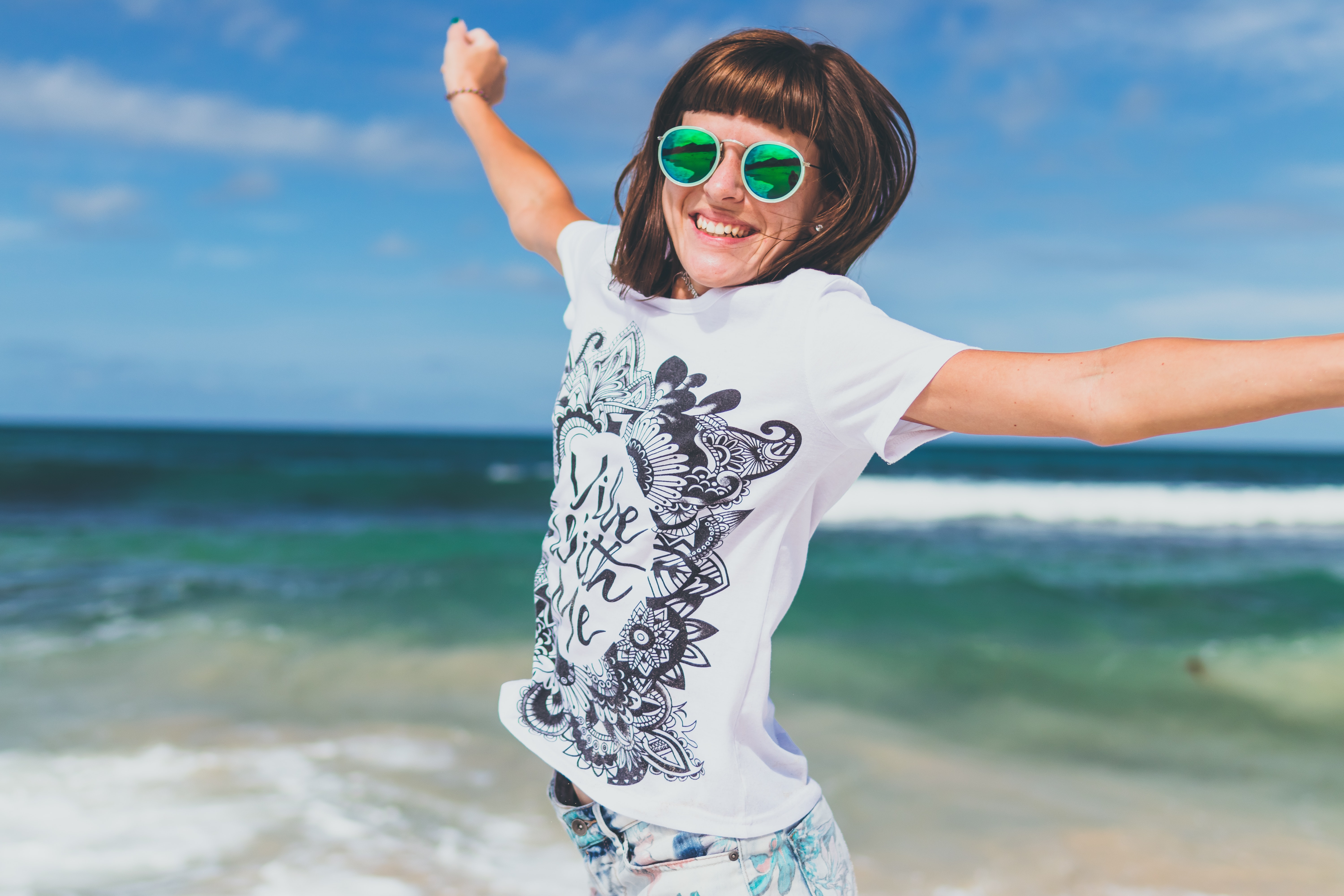 Woman in White and Black T-shirt Lifting Hands Smiling on Seashore, Attractive, Outside, Woman, Waves, HQ Photo