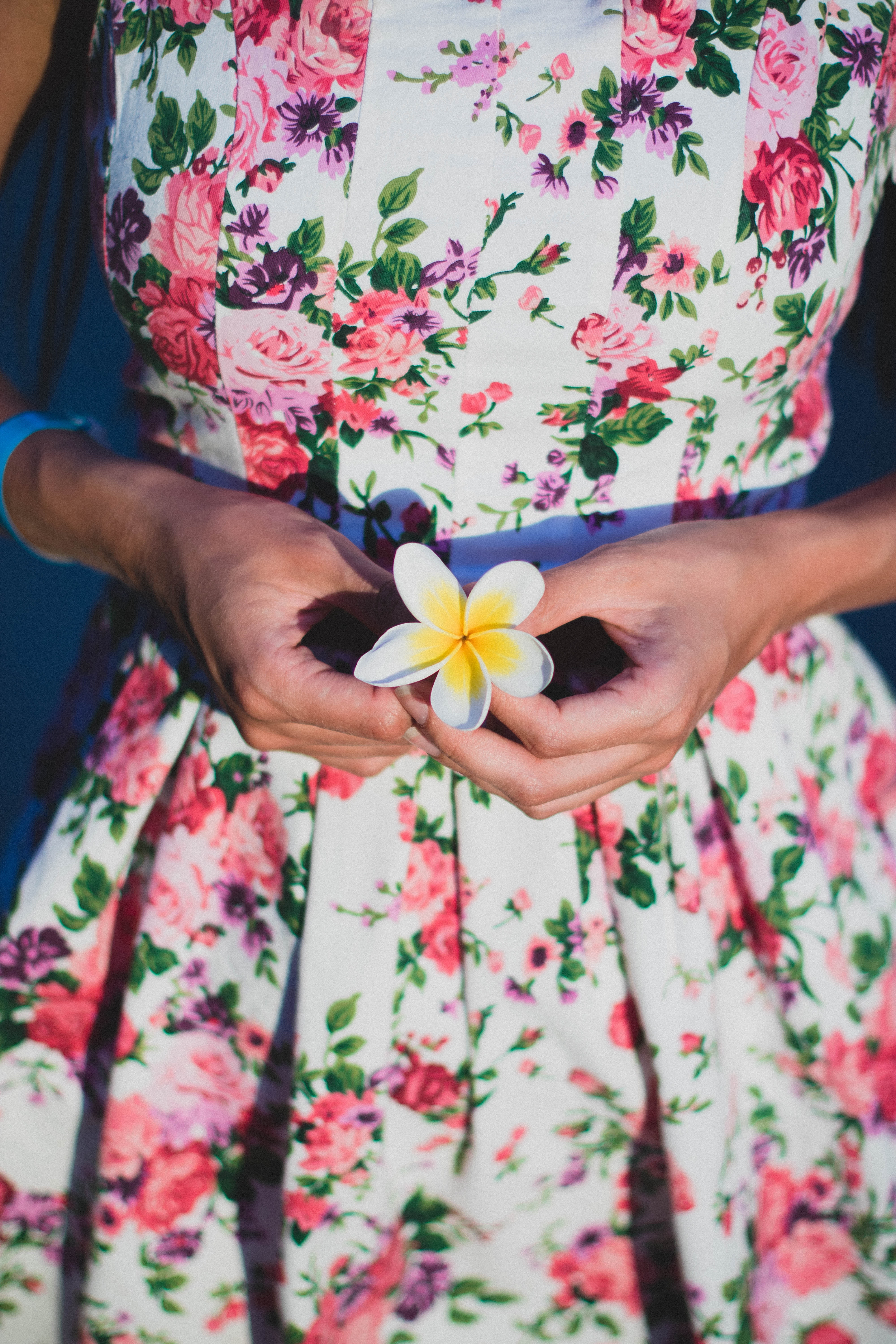 Woman in white and green floral dress holding flower photo