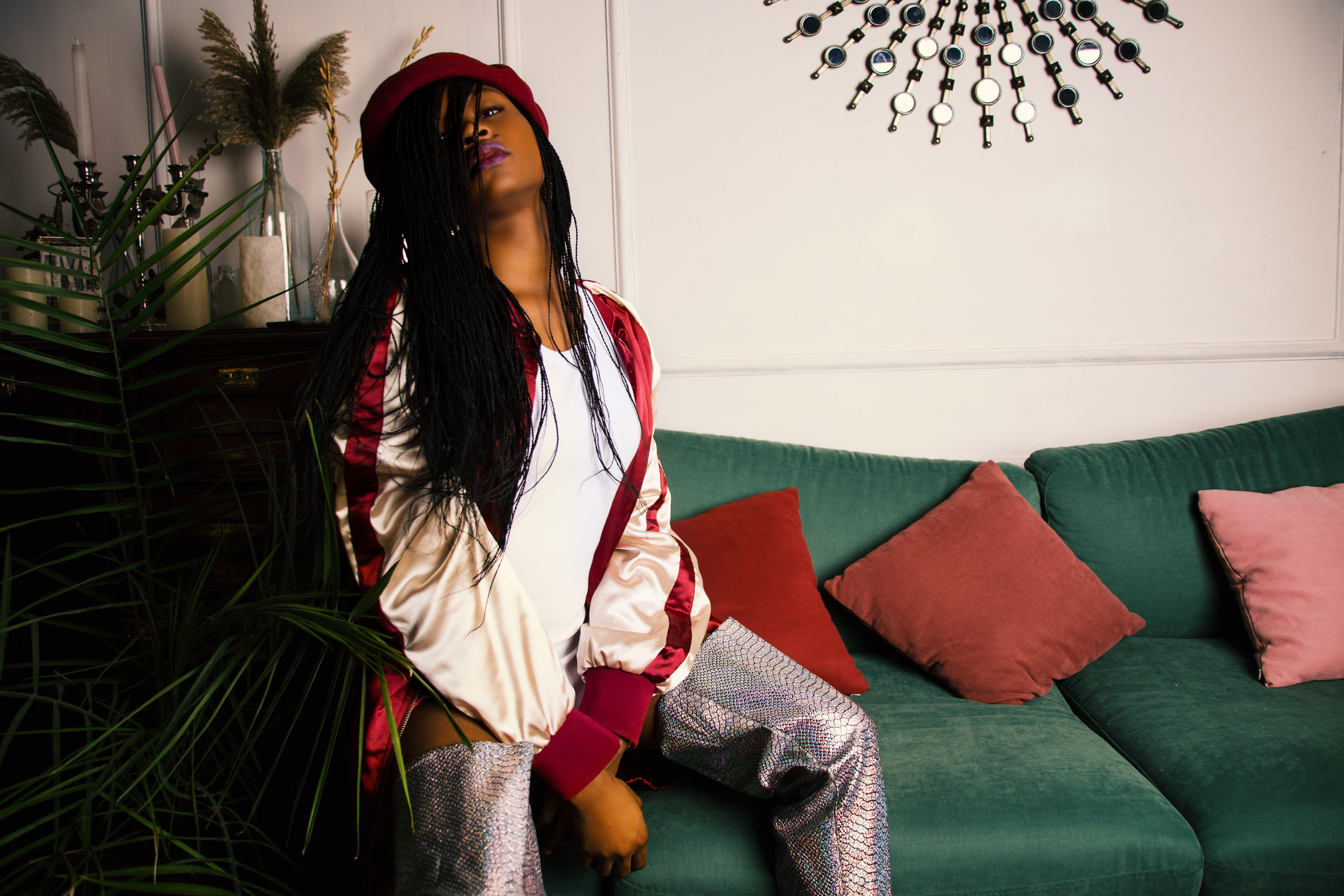 Woman in white and red jacket sitting on green couch photo