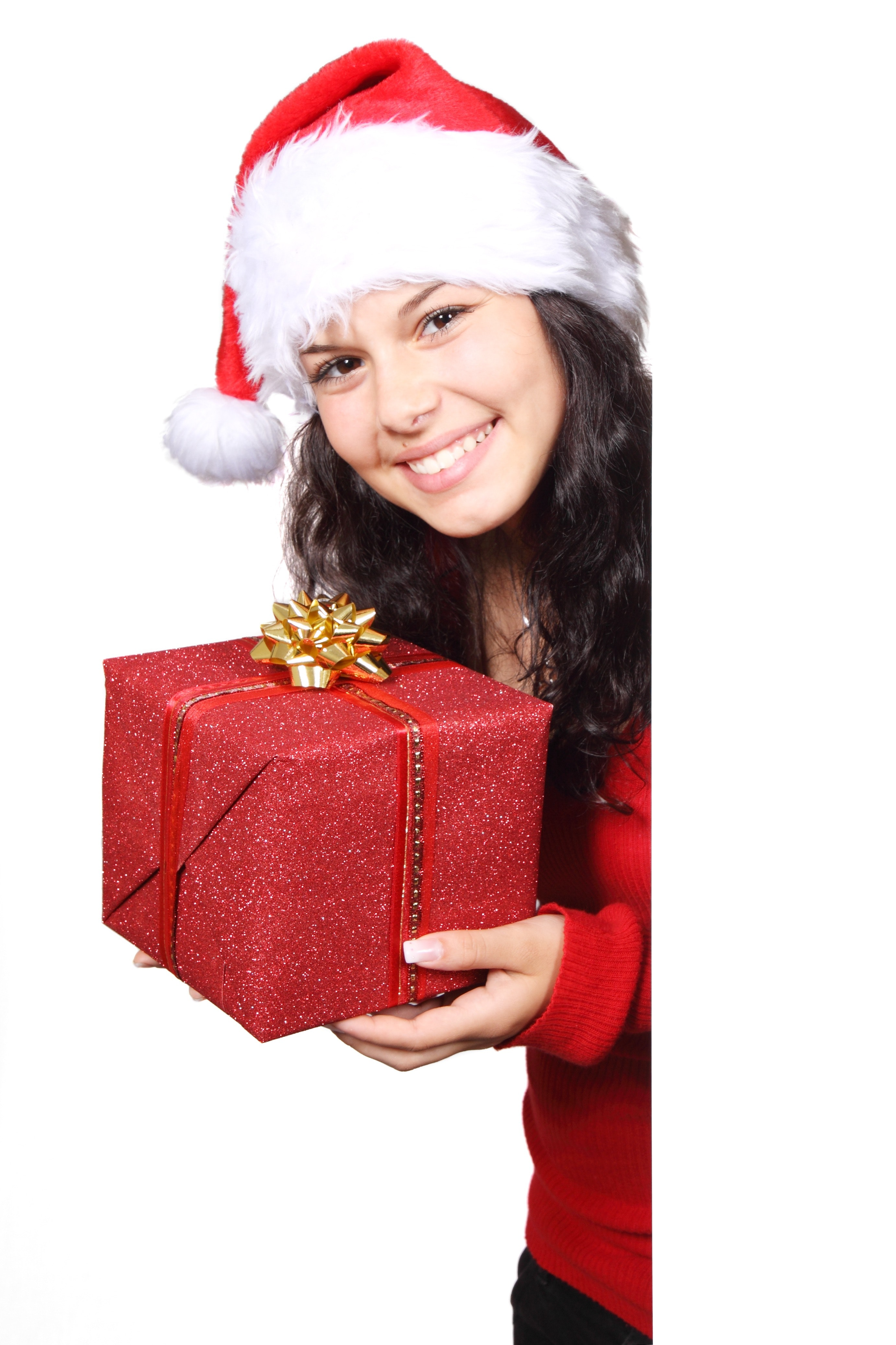 Woman in white and red santa hat holding red christmas gift photo