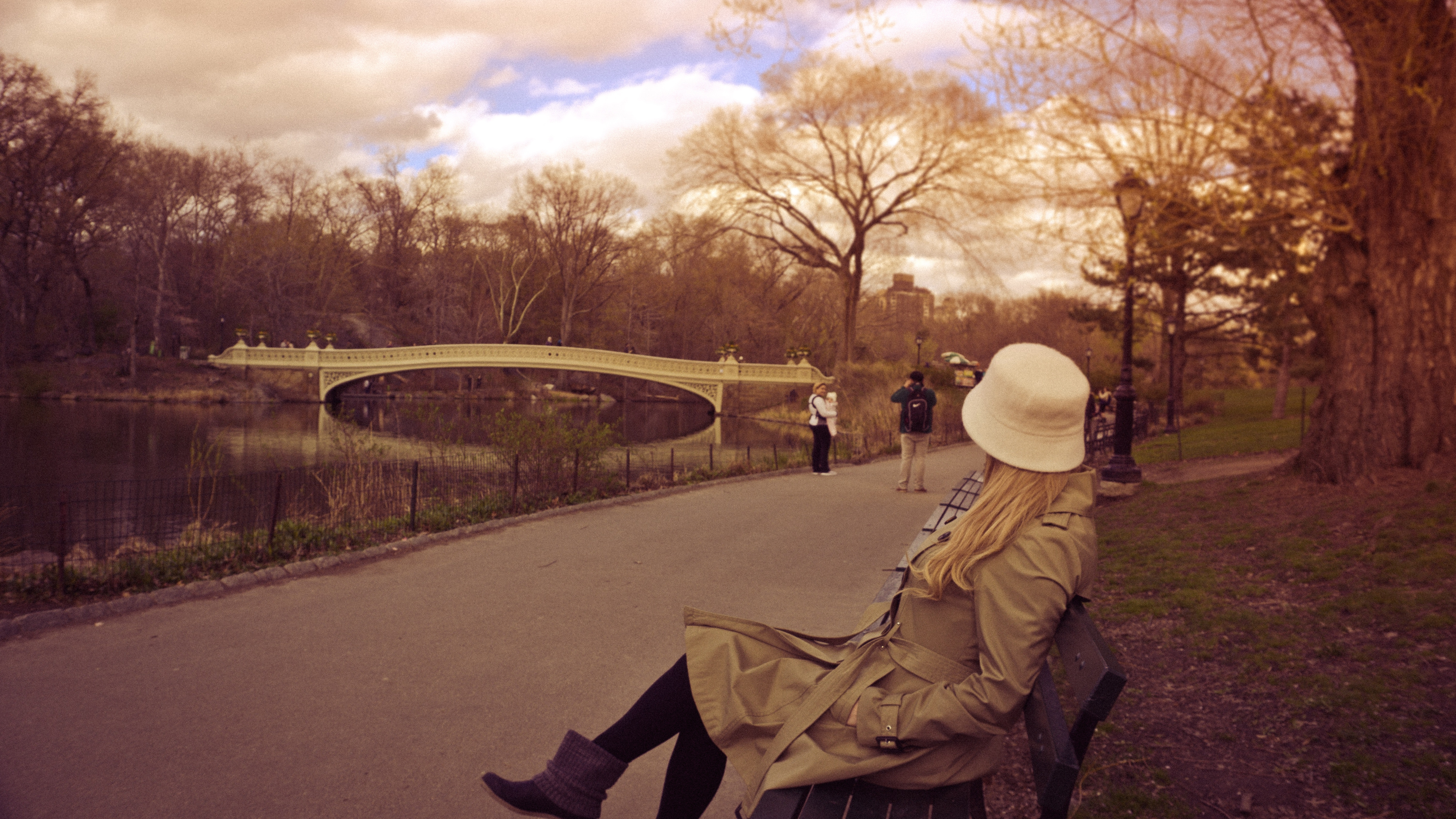Woman in white bucket hat, brown coat and boots sitting on bench at park photo
