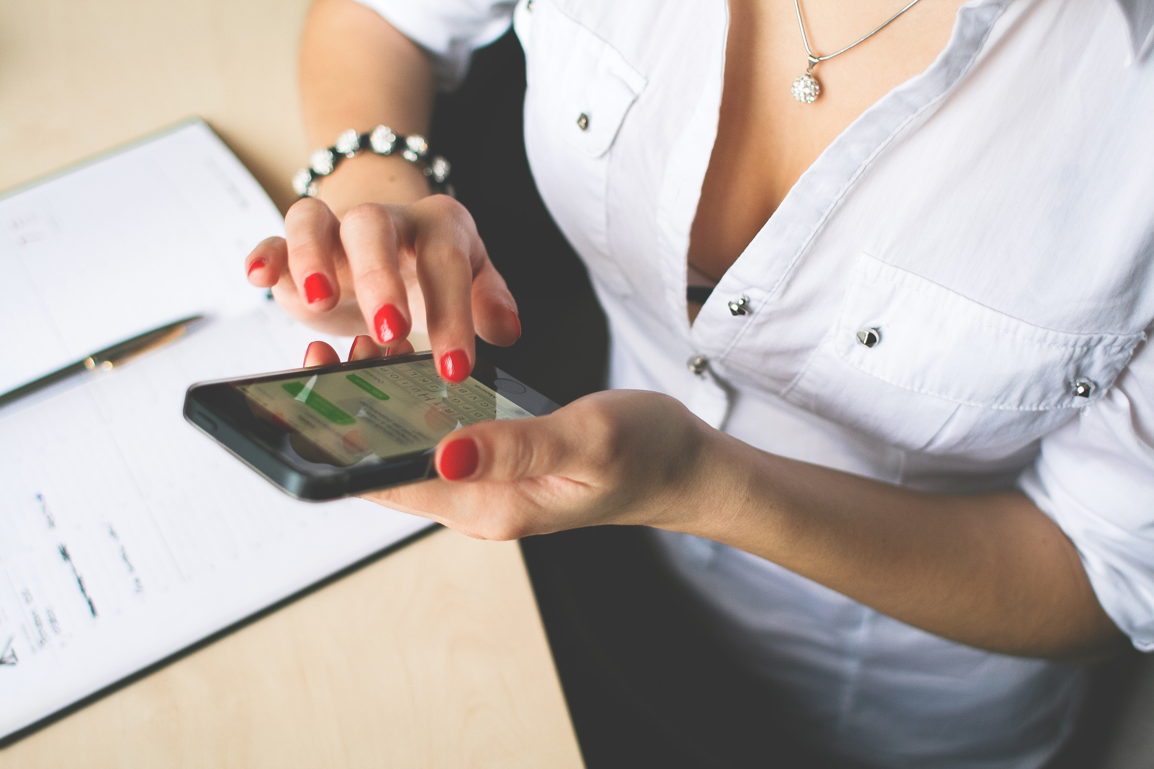 Woman in white button up top and holding black android smartphone photo