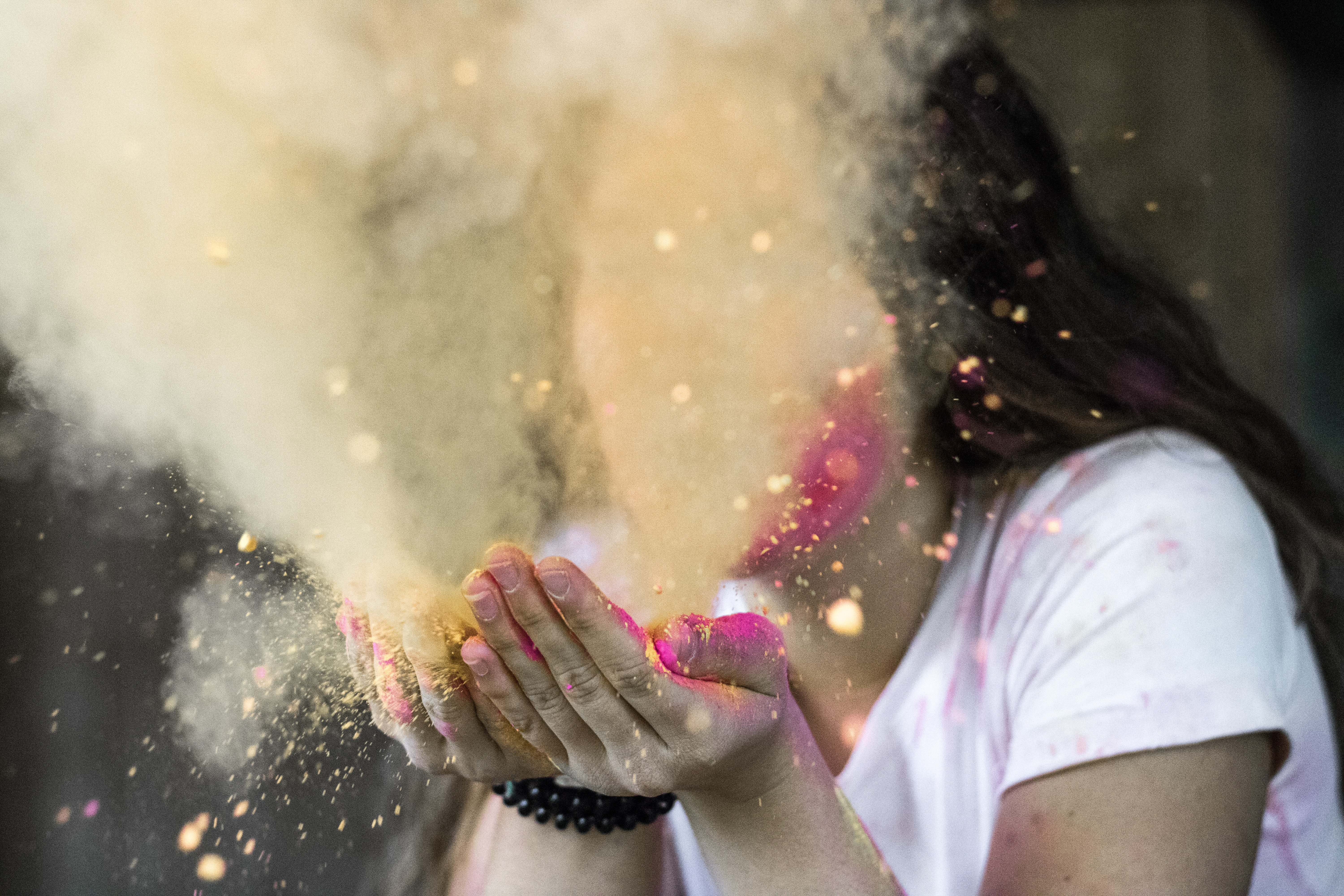 Woman in white cap-sleeved shirt blowing dust photo