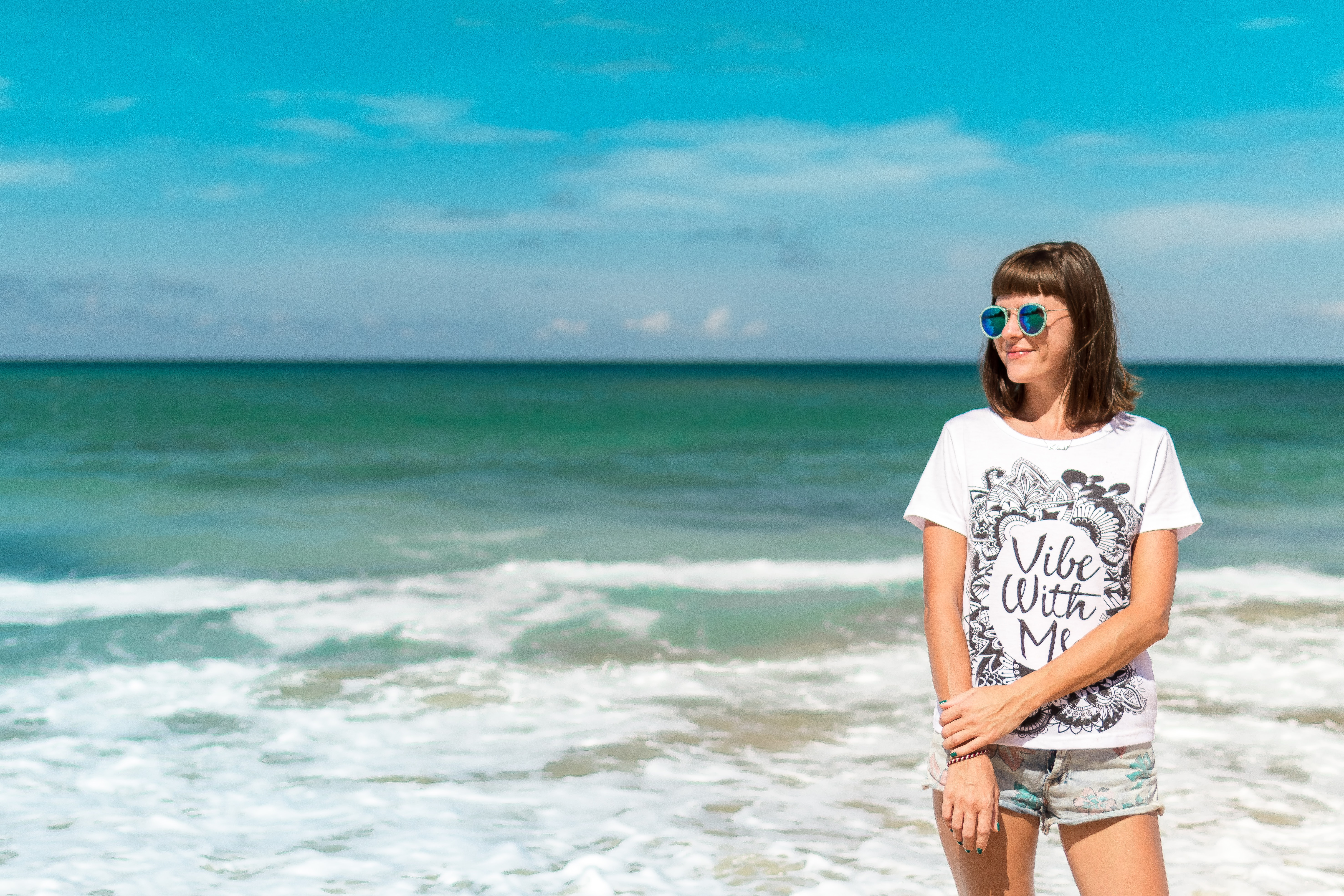 Woman in white crew-neck shirt near sea shore photo
