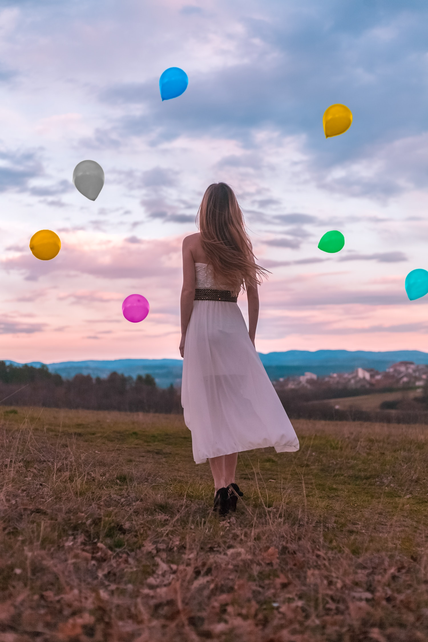 Woman in white dress looking at the balloons photo
