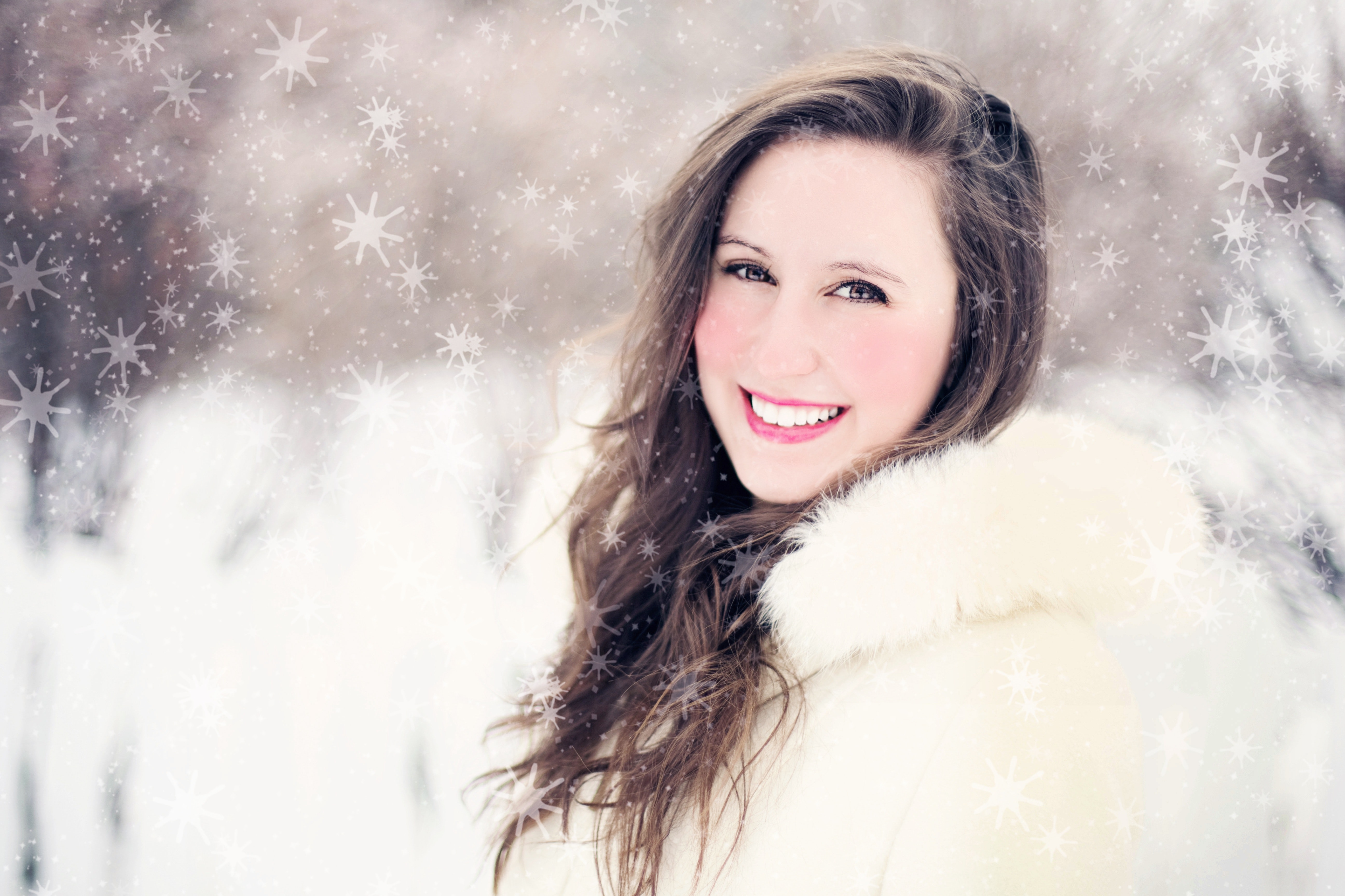 Woman in white furred jacket smiling in front photo
