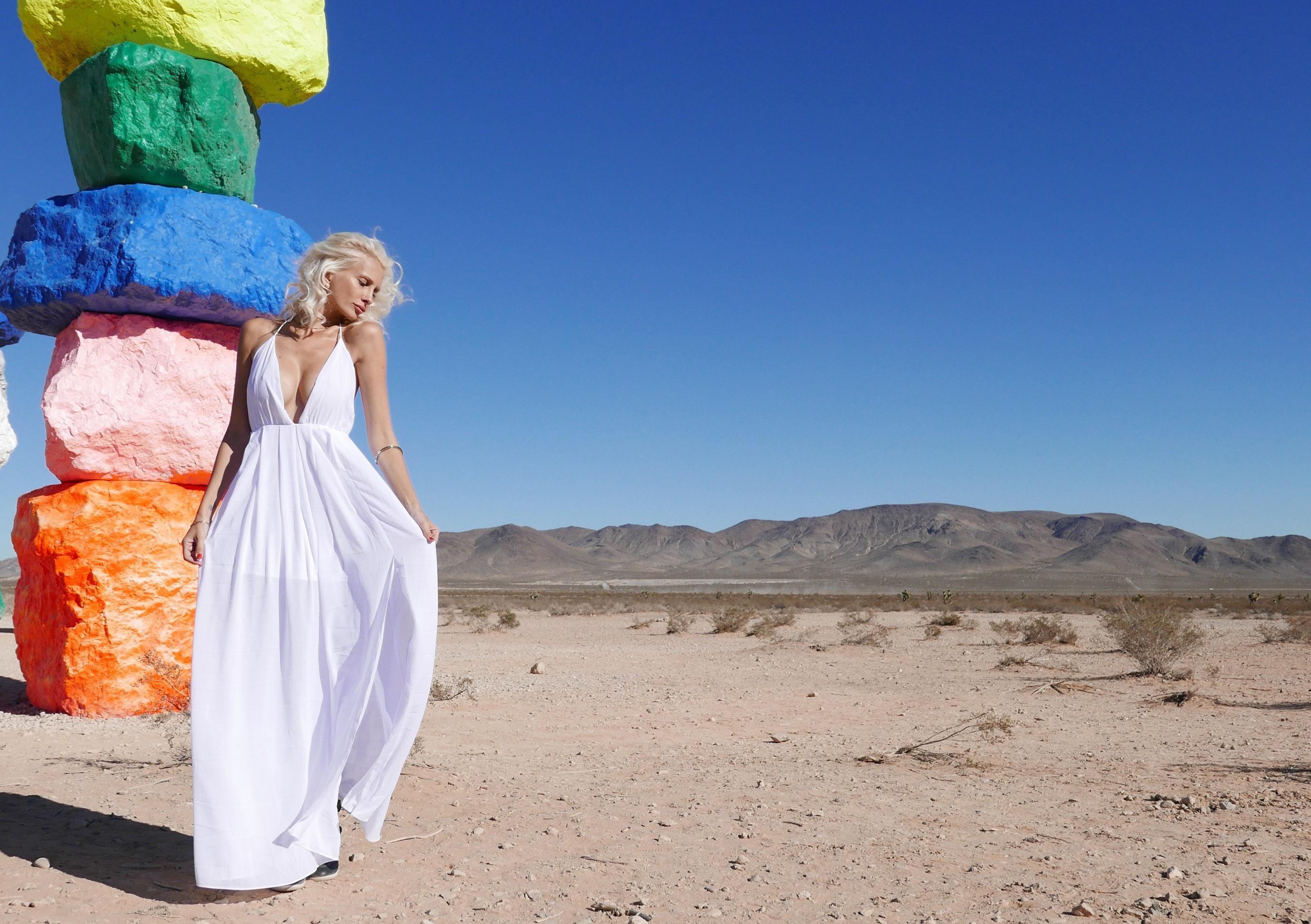 Woman in white halter neckline deep v-neck dress standing photo