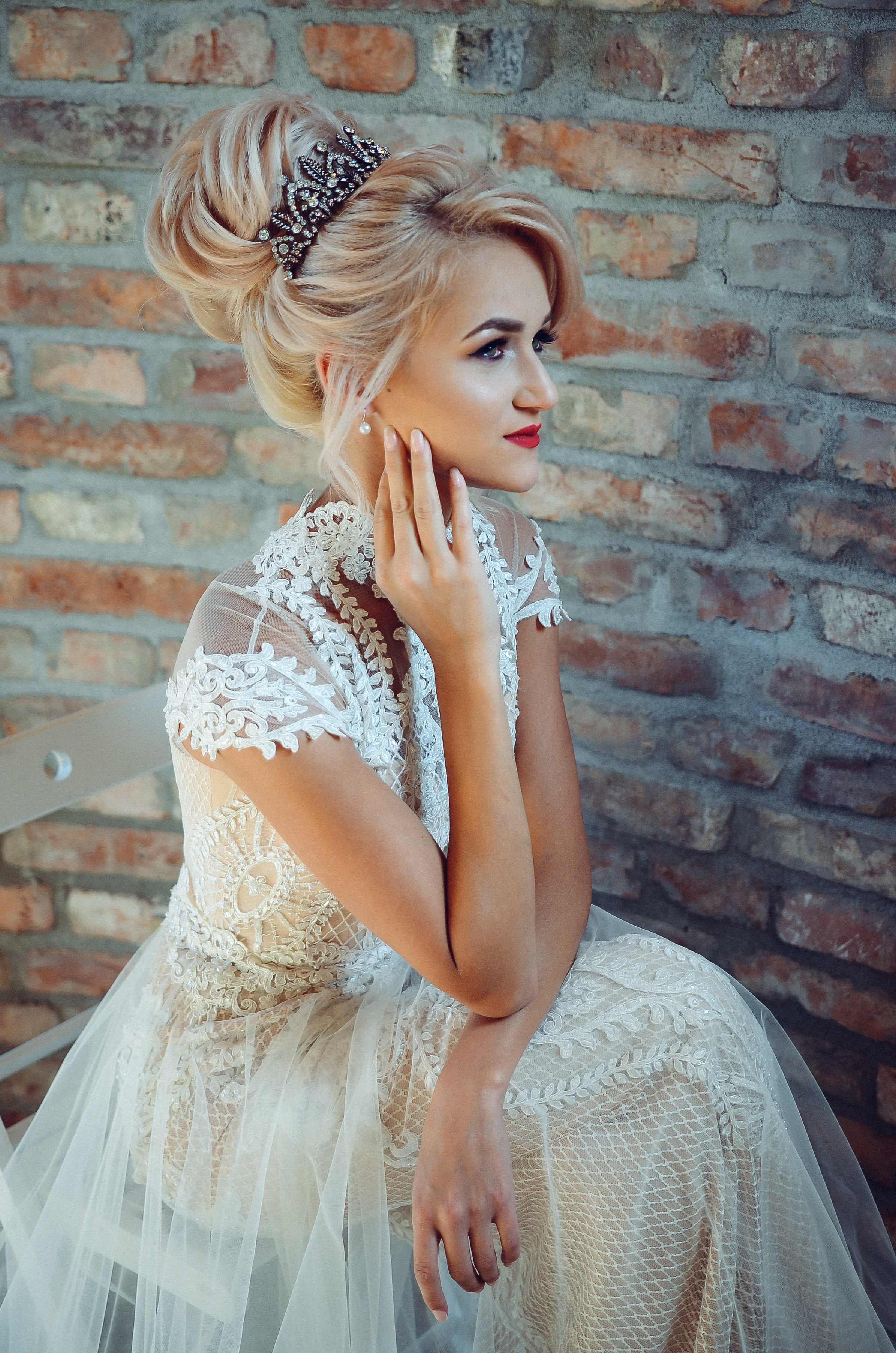 Woman in white lace dress sits on chair photo
