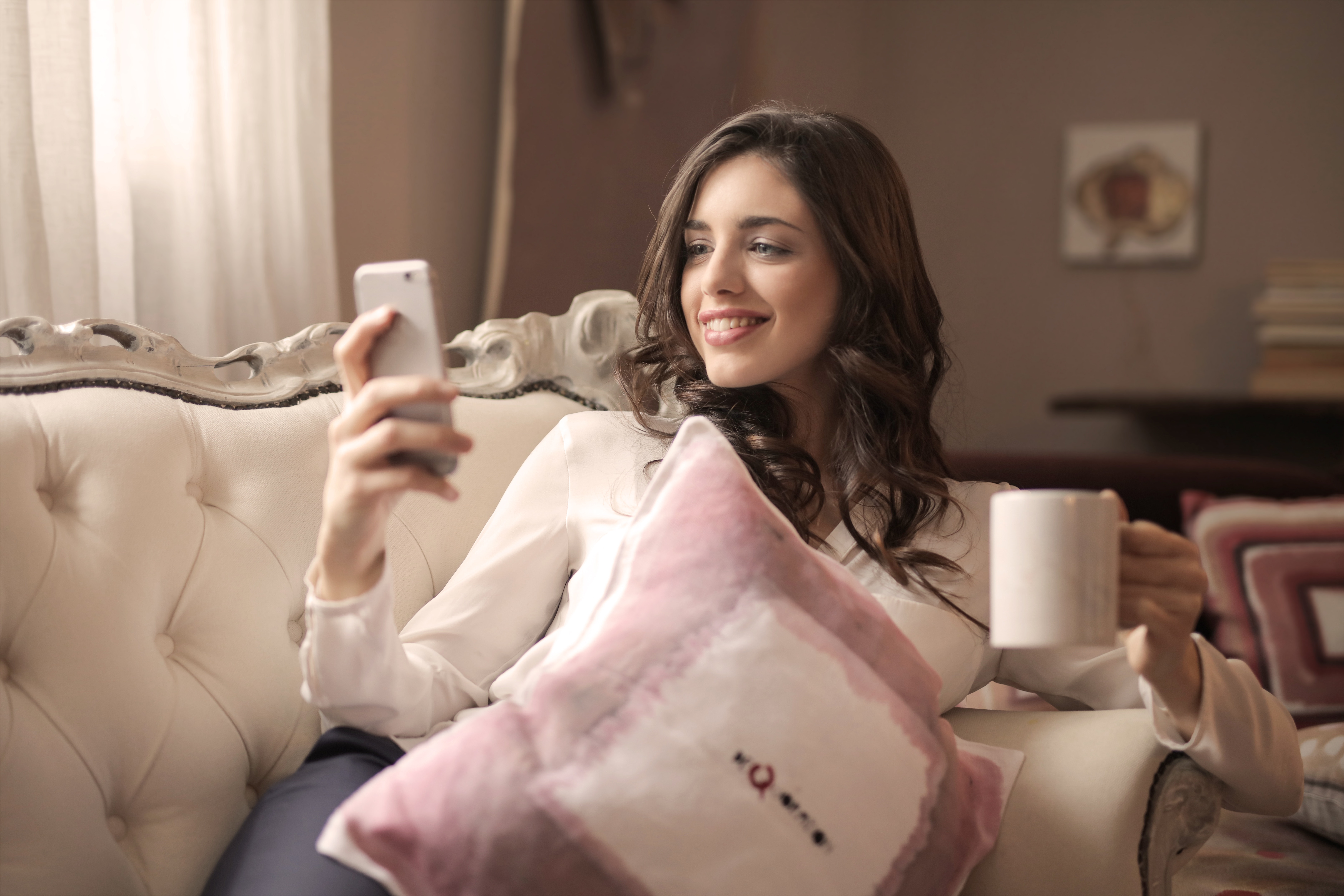 Woman in white long-sleeved shirt holding smartphone sitting on tufted sofa photo