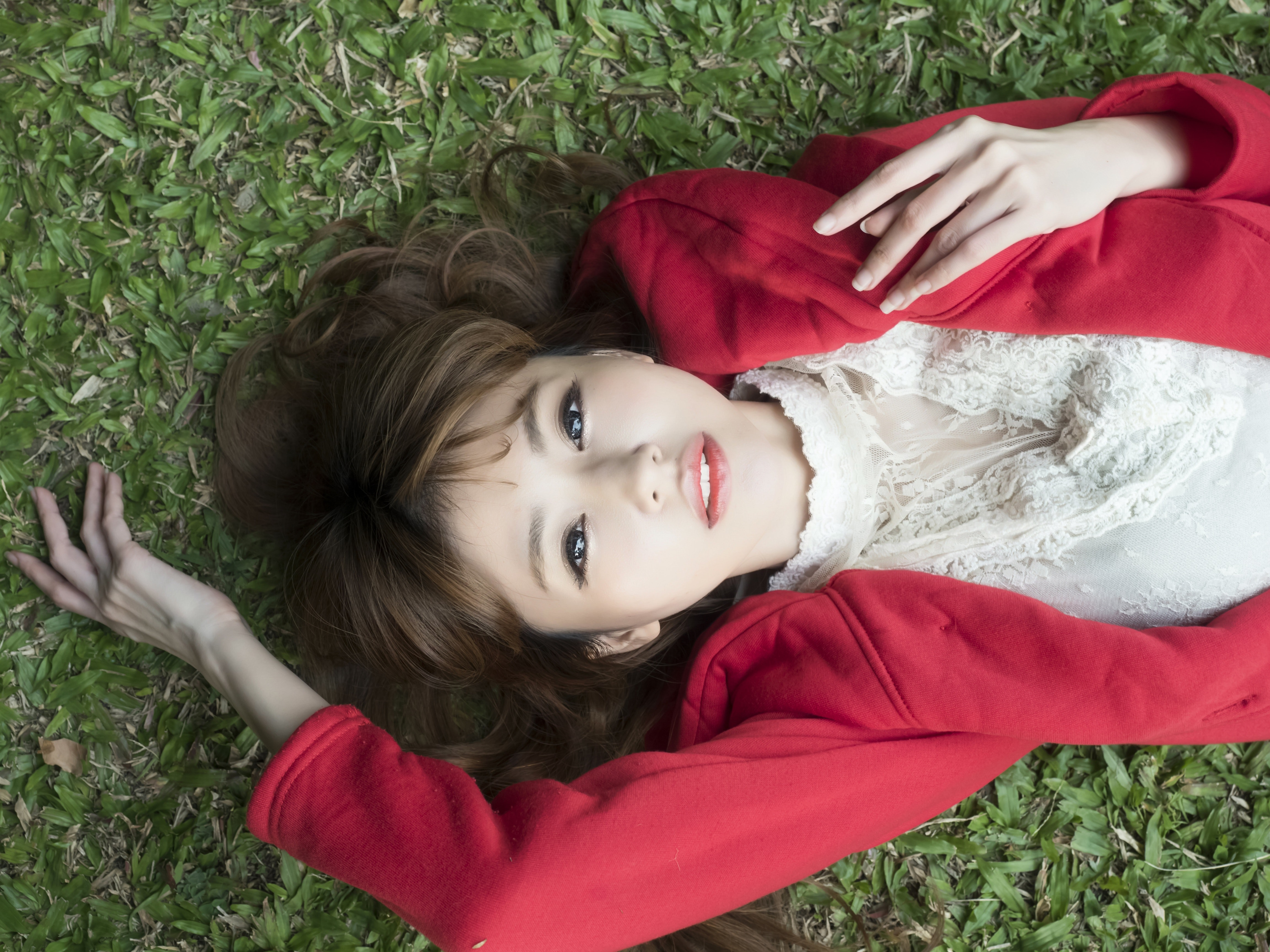 Woman in white shirt wearing red blazer lying on green grass photo