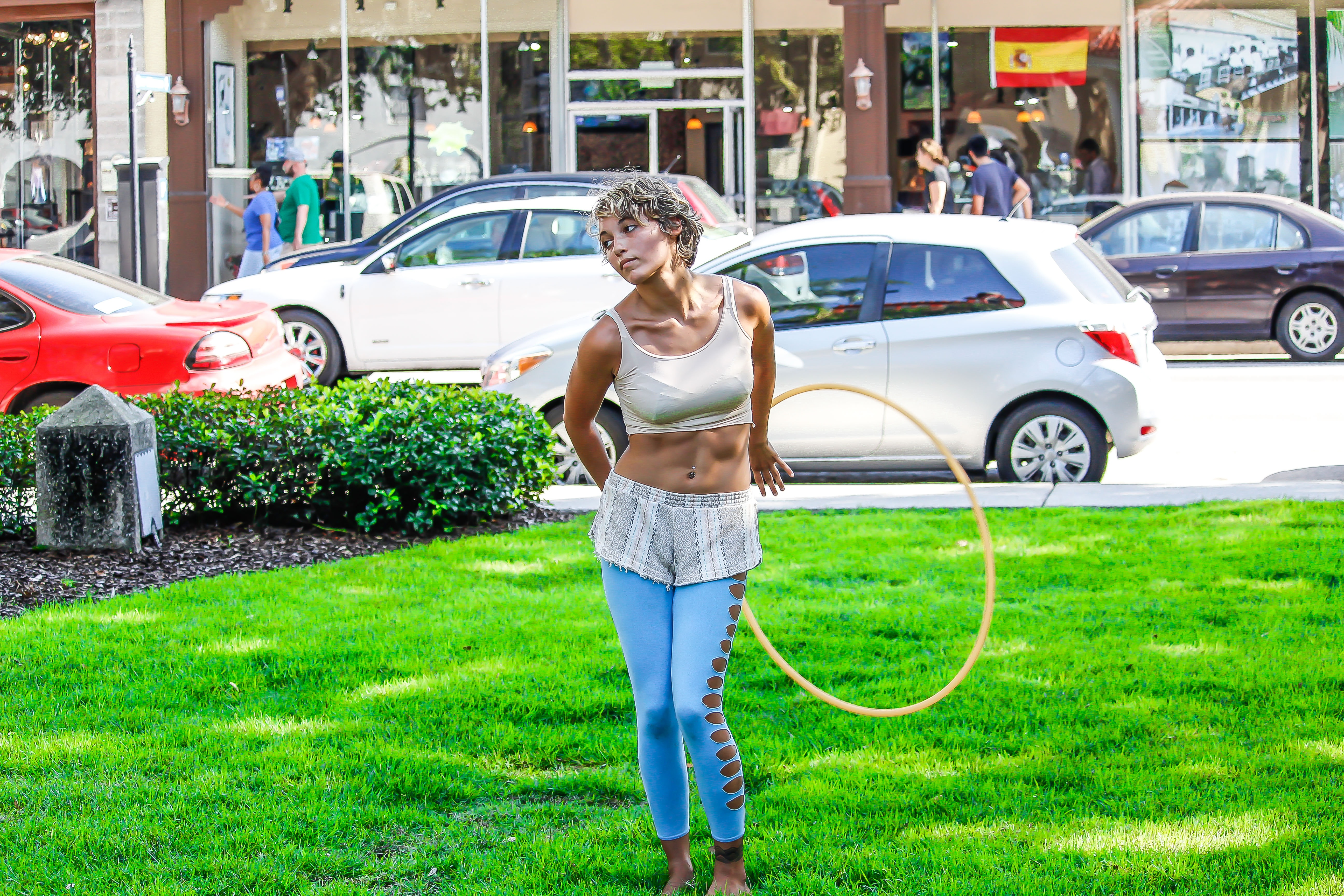 Woman in white sleeveless shirt and blue pants holds yellow hula hoop stands on green grass photo