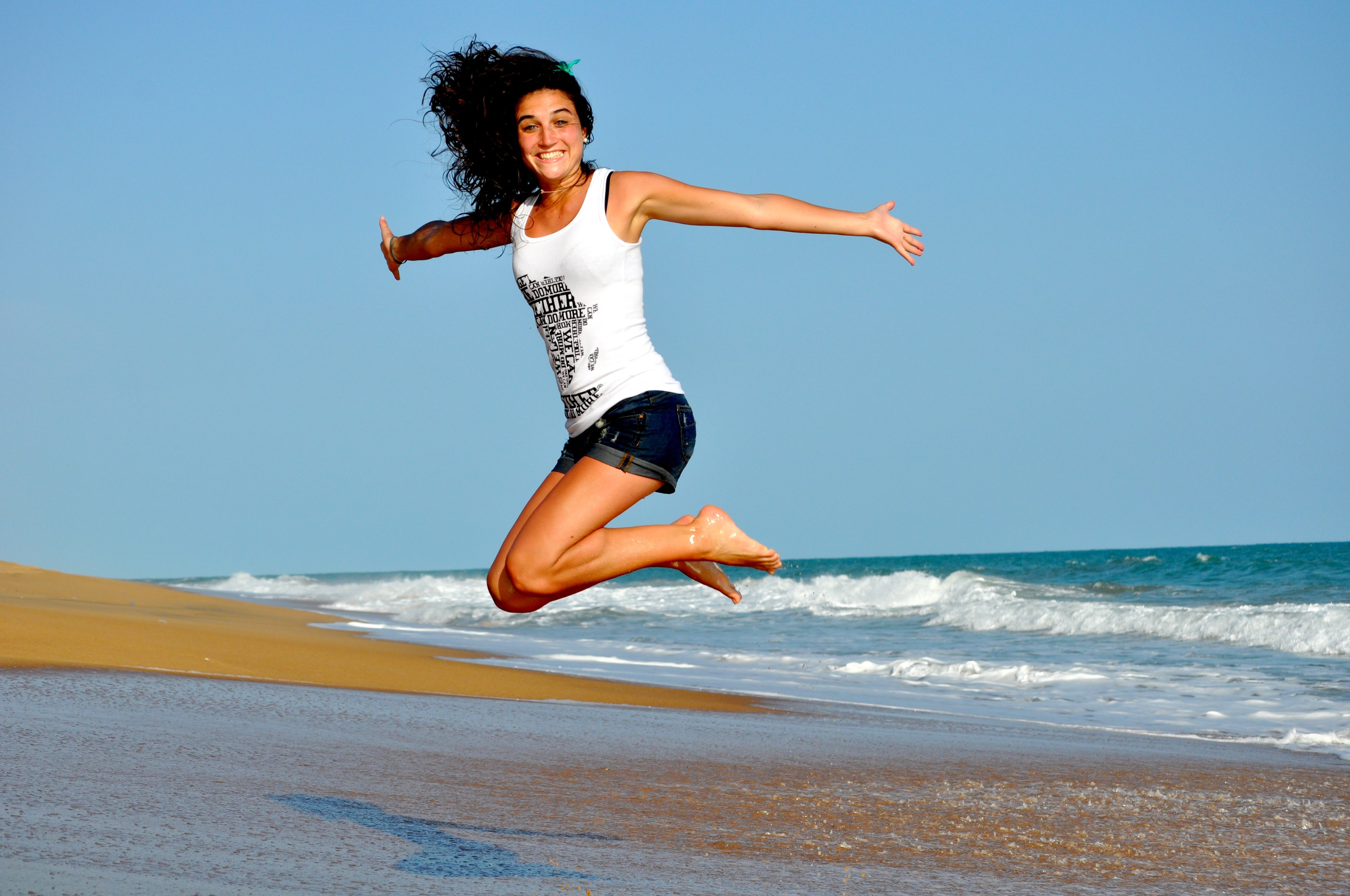 Woman in White Tanktop Jump over Beach Sand, Beach, Beautiful, Content, Happy, HQ Photo