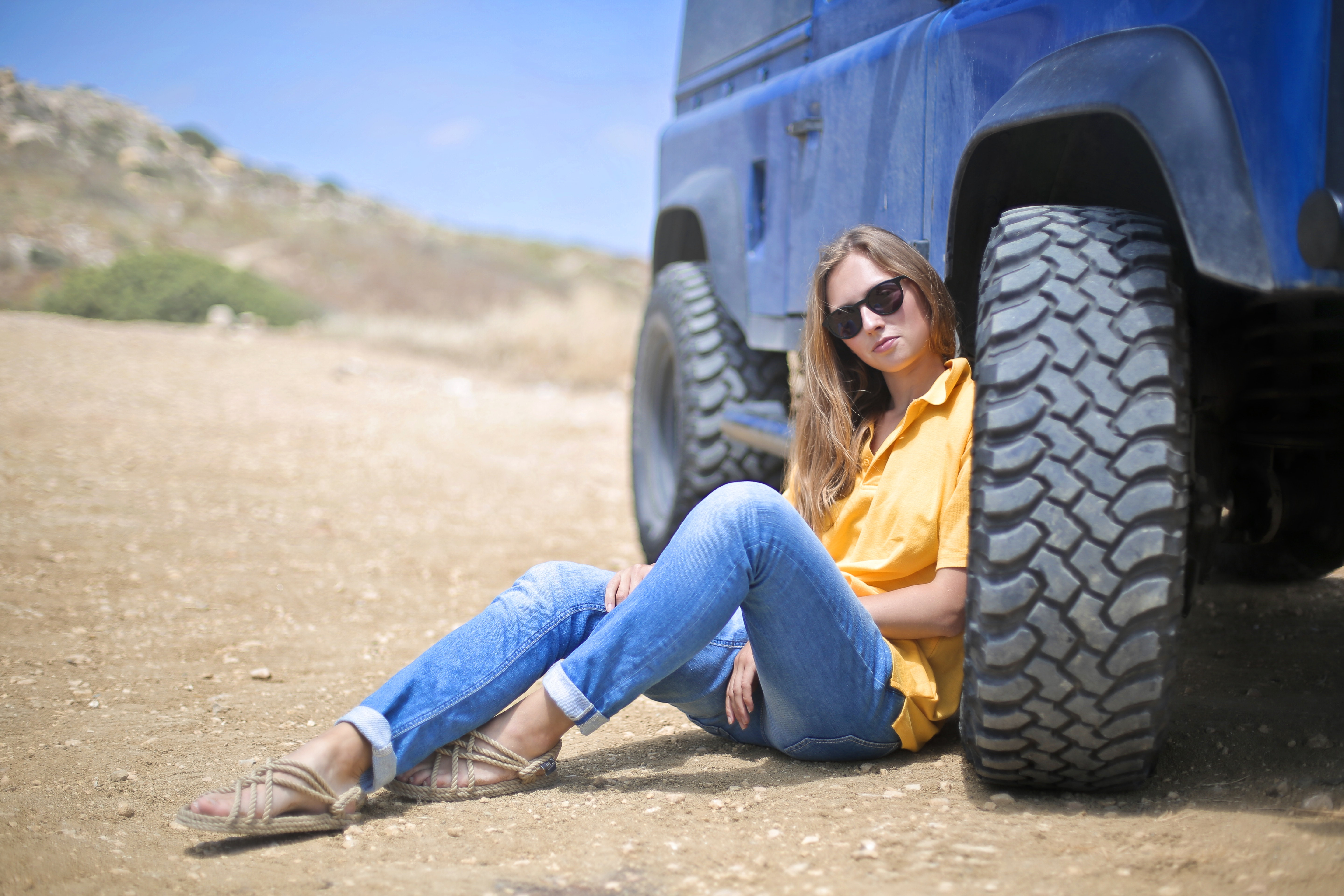 Woman in Yellow Polo Shirt Sitting on Ground Leaning on Blue Vehicle at Daytime, Adult, Offroad, Wheel, Wear, HQ Photo