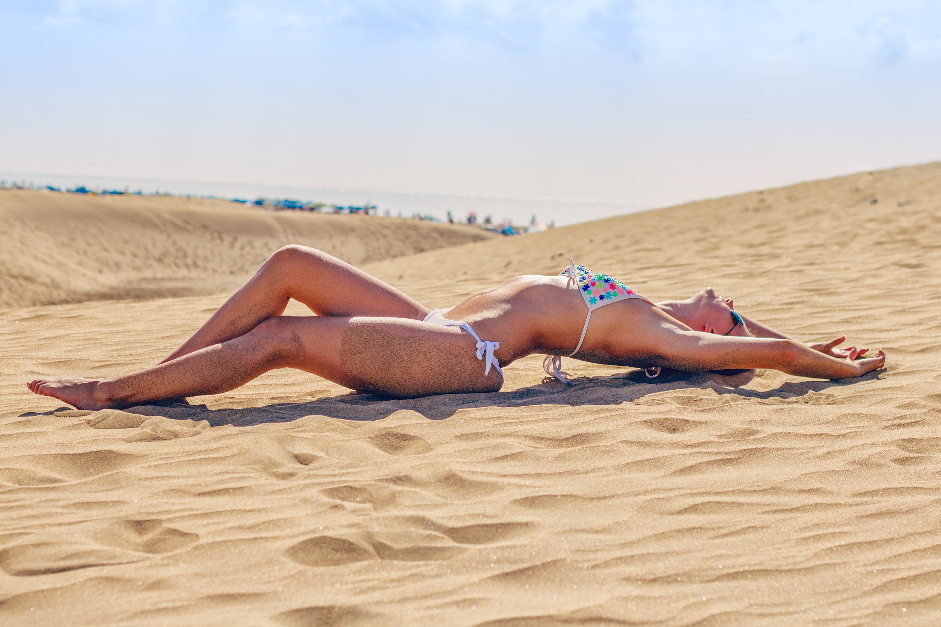 Woman lying on sand at beach photo