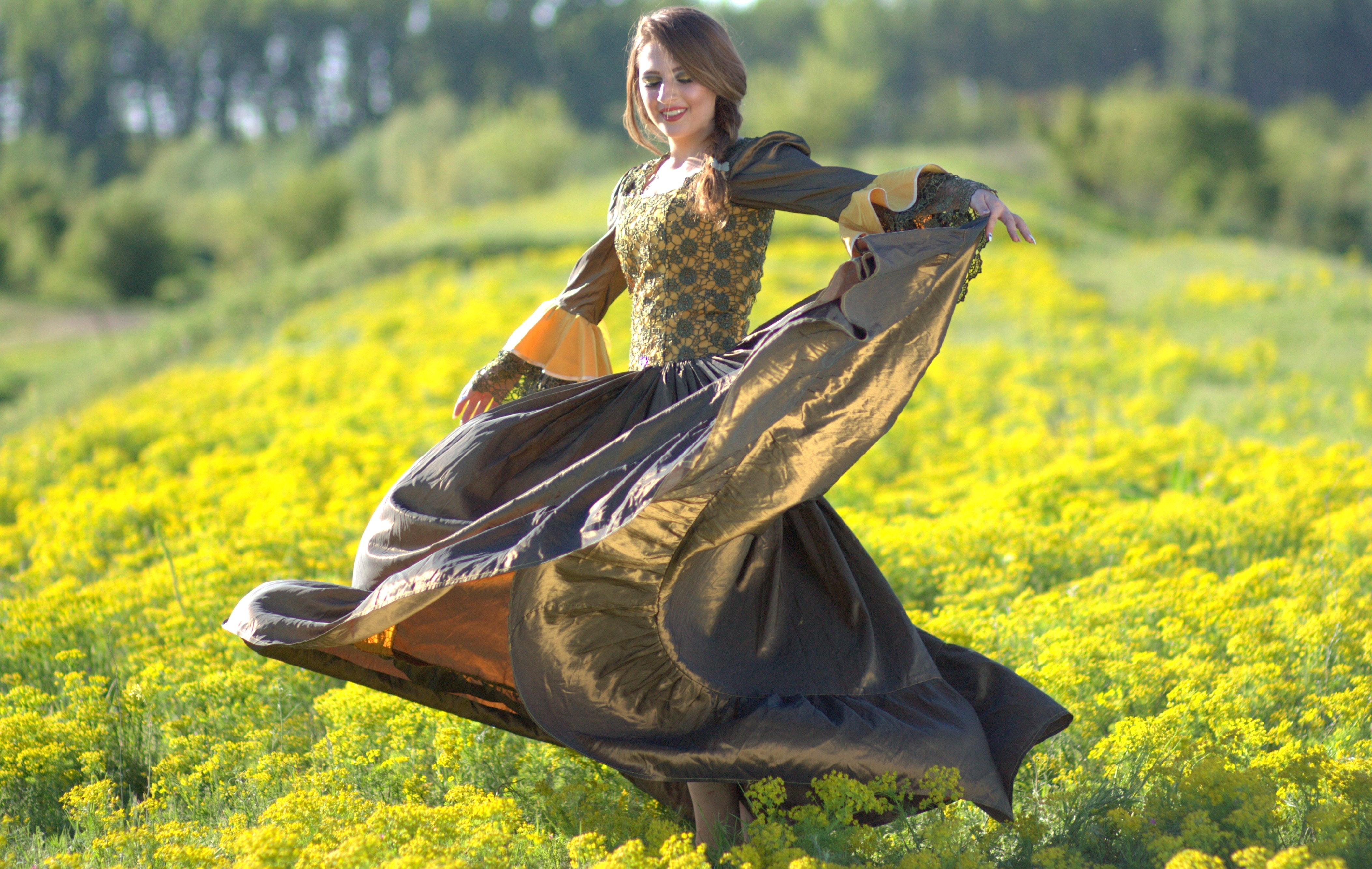 Woman on princess costume waving her dress on green flower fields photo