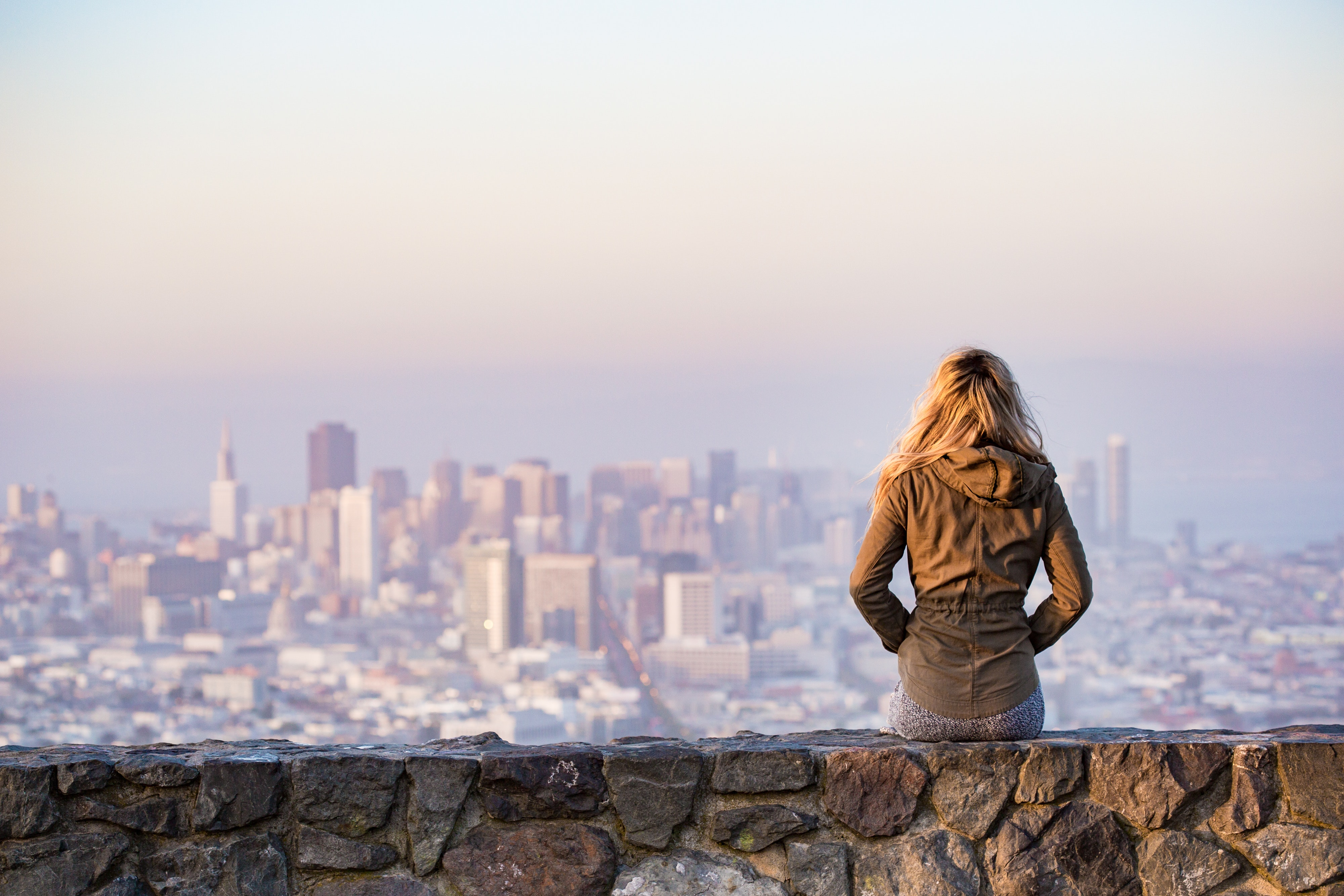 Woman on rock platform viewing city photo