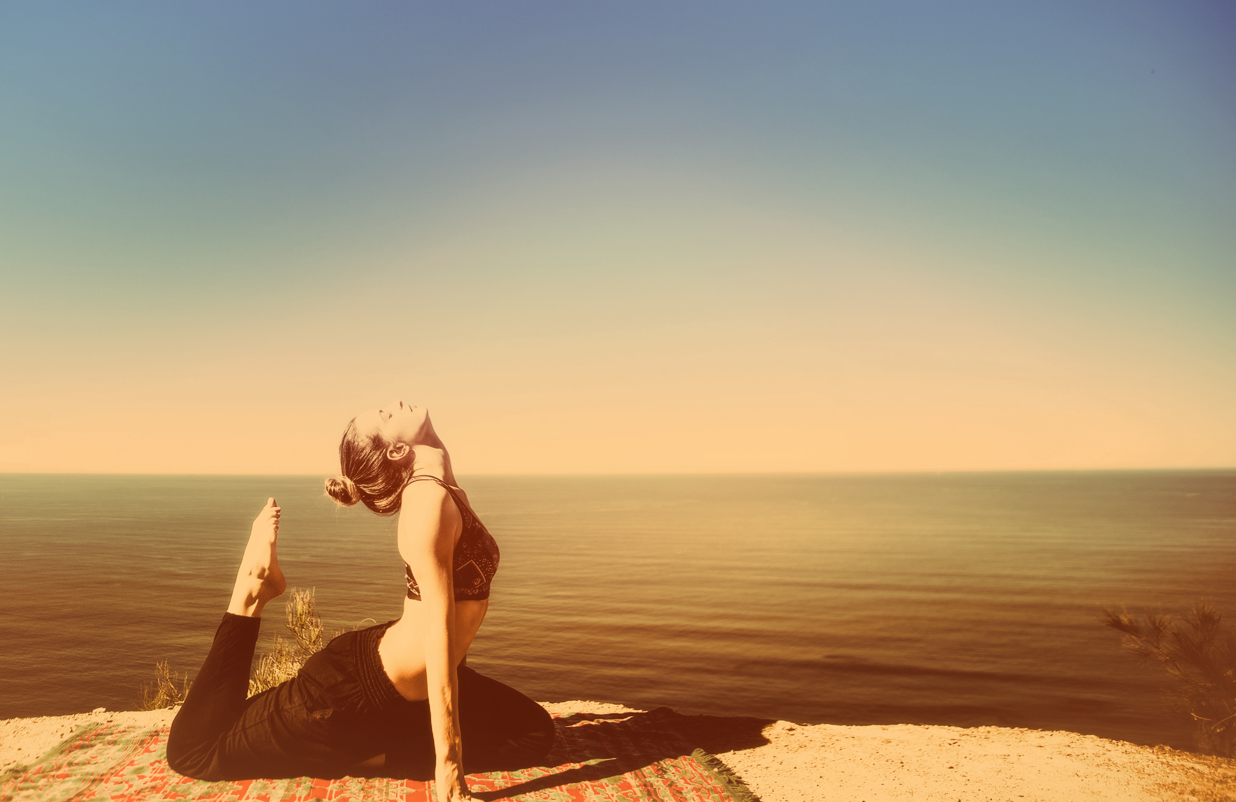 Woman practicing yoga by the ocean - metal toned photo