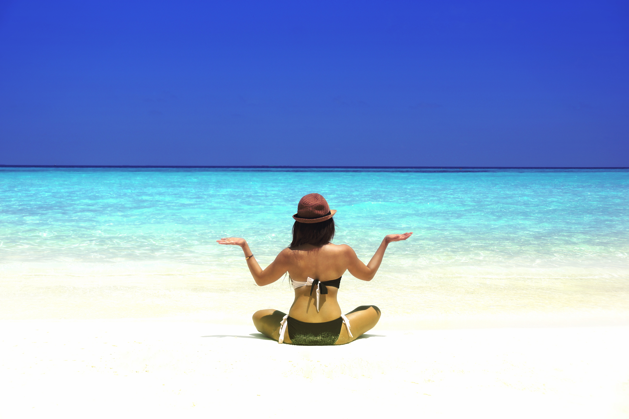 Woman practicing yoga on the beach - vivid colors photo