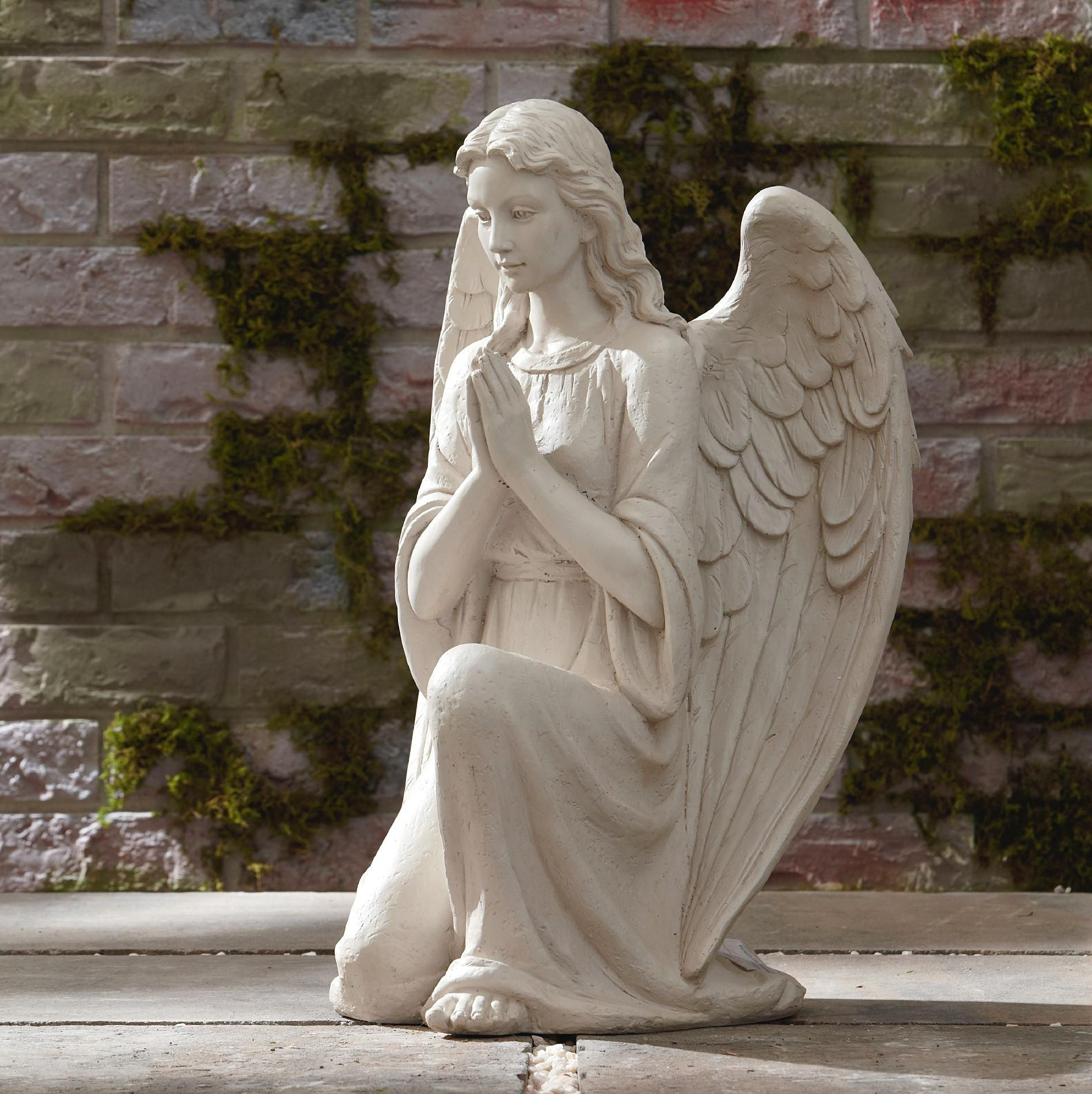 This little cherubic angel statue is sitting with hands over one ...