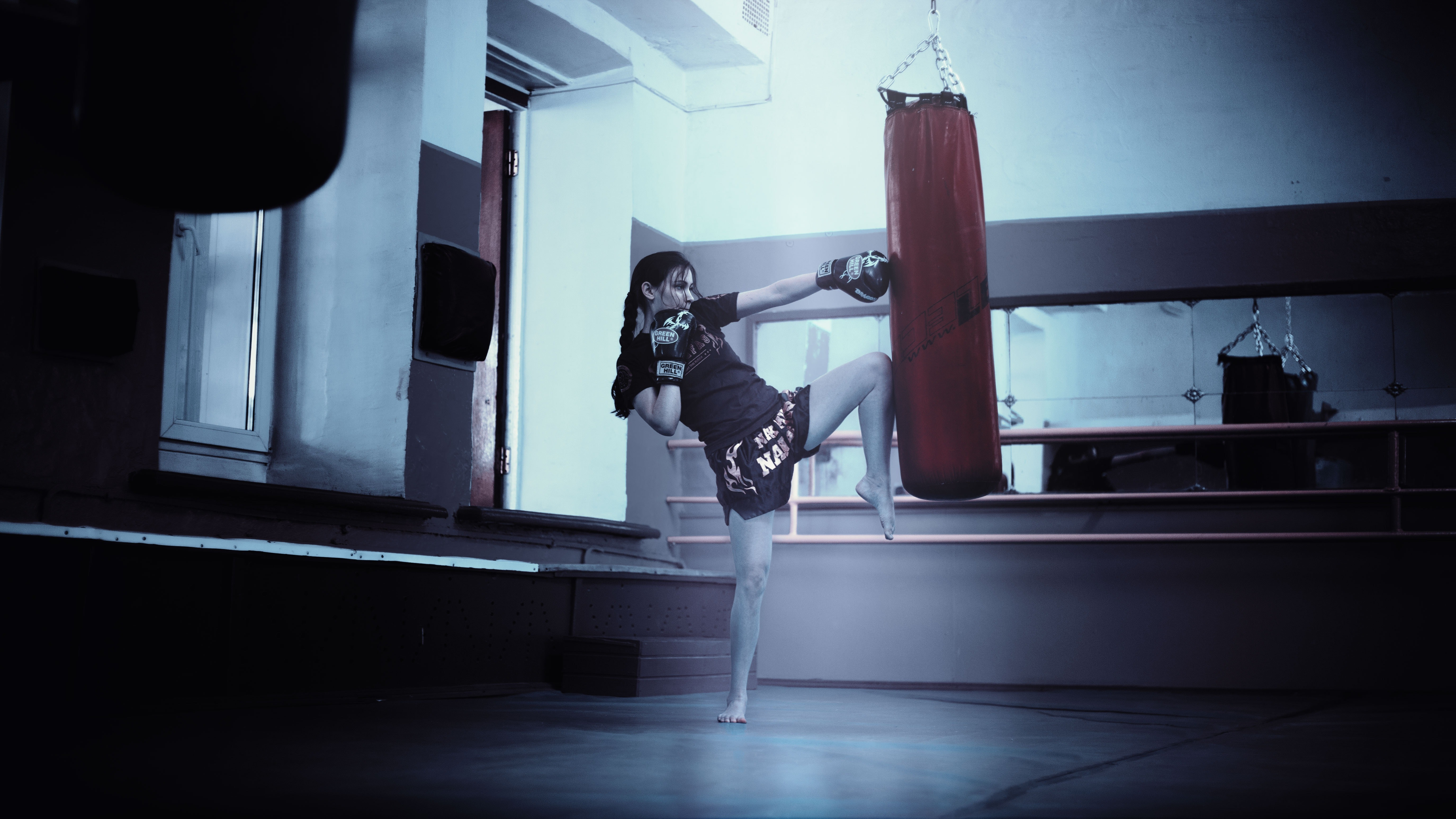 Woman punching red heavy bag photo