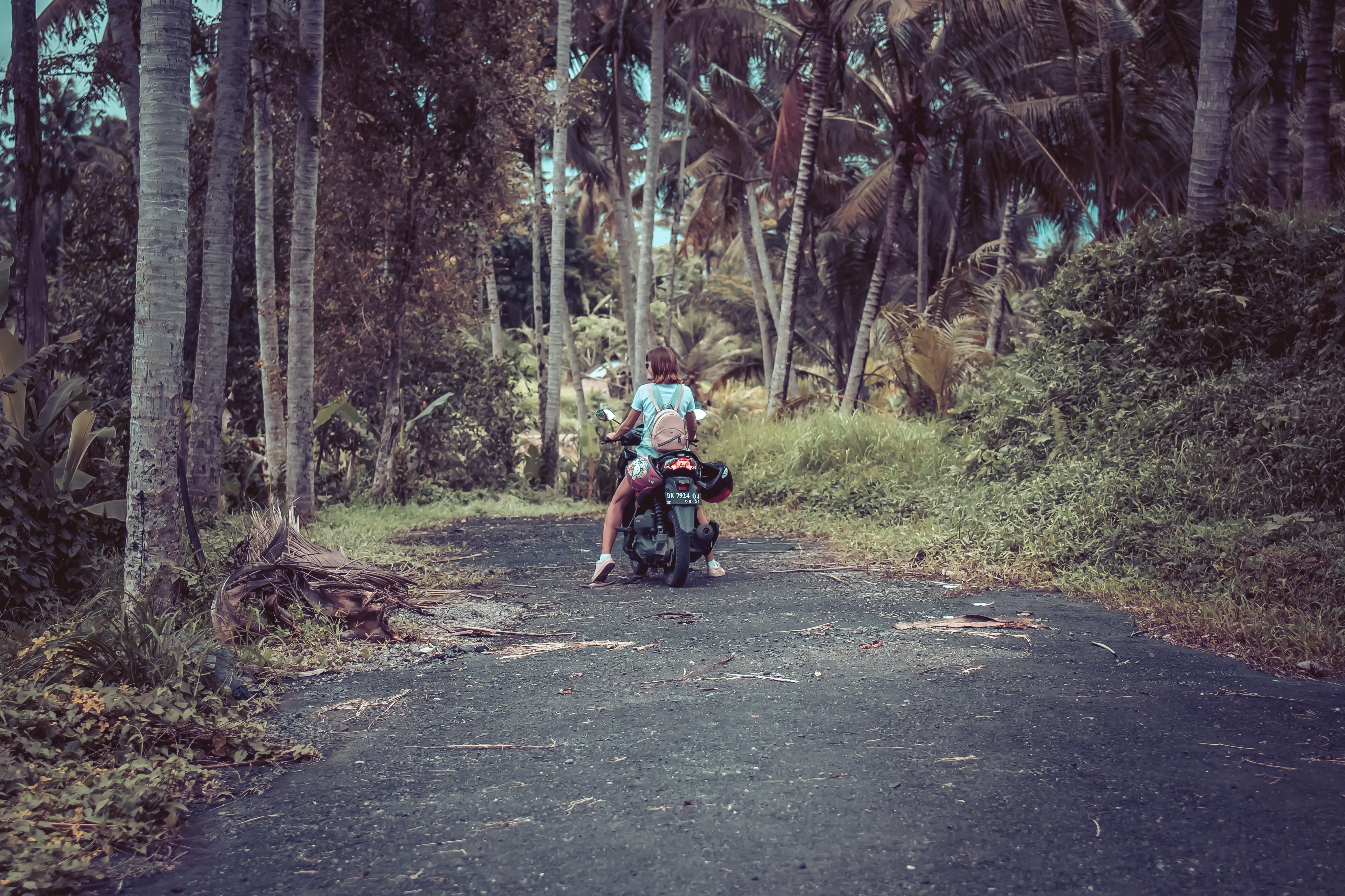 Woman riding motor scooter near coconut trees photo