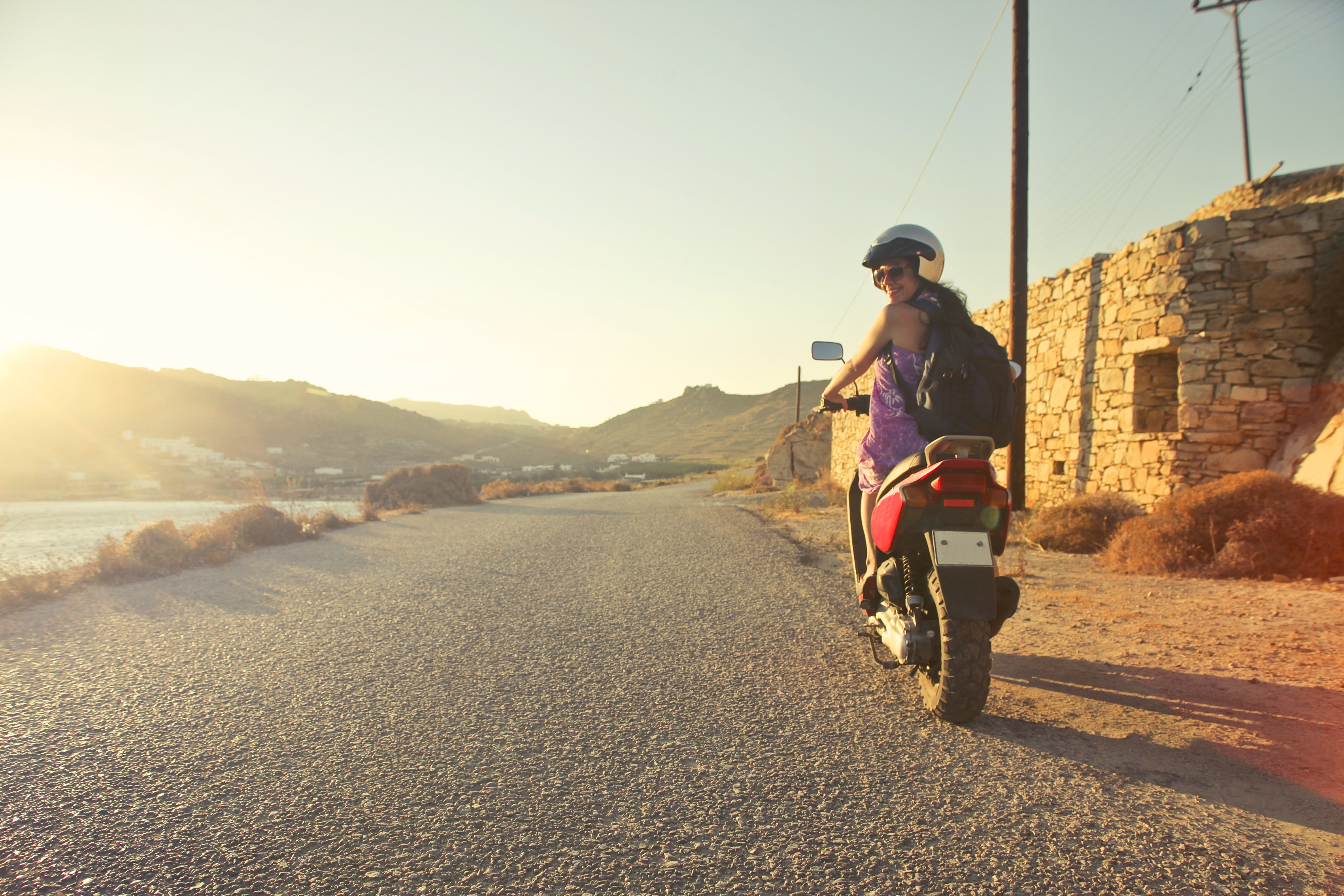 Woman riding motor scooter travelling on asphalt road during sunrise photo