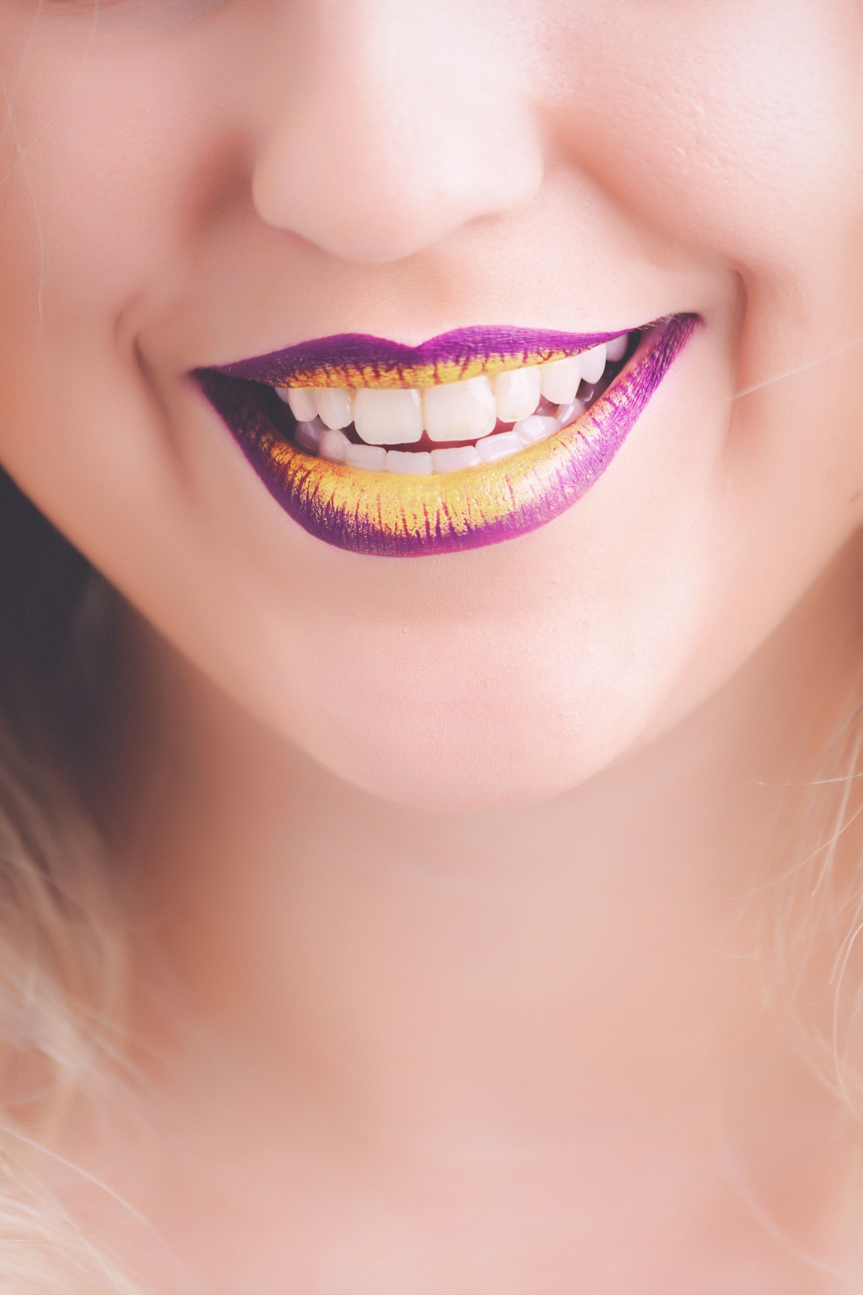 Woman showing her purple and yellow lipsticks photo