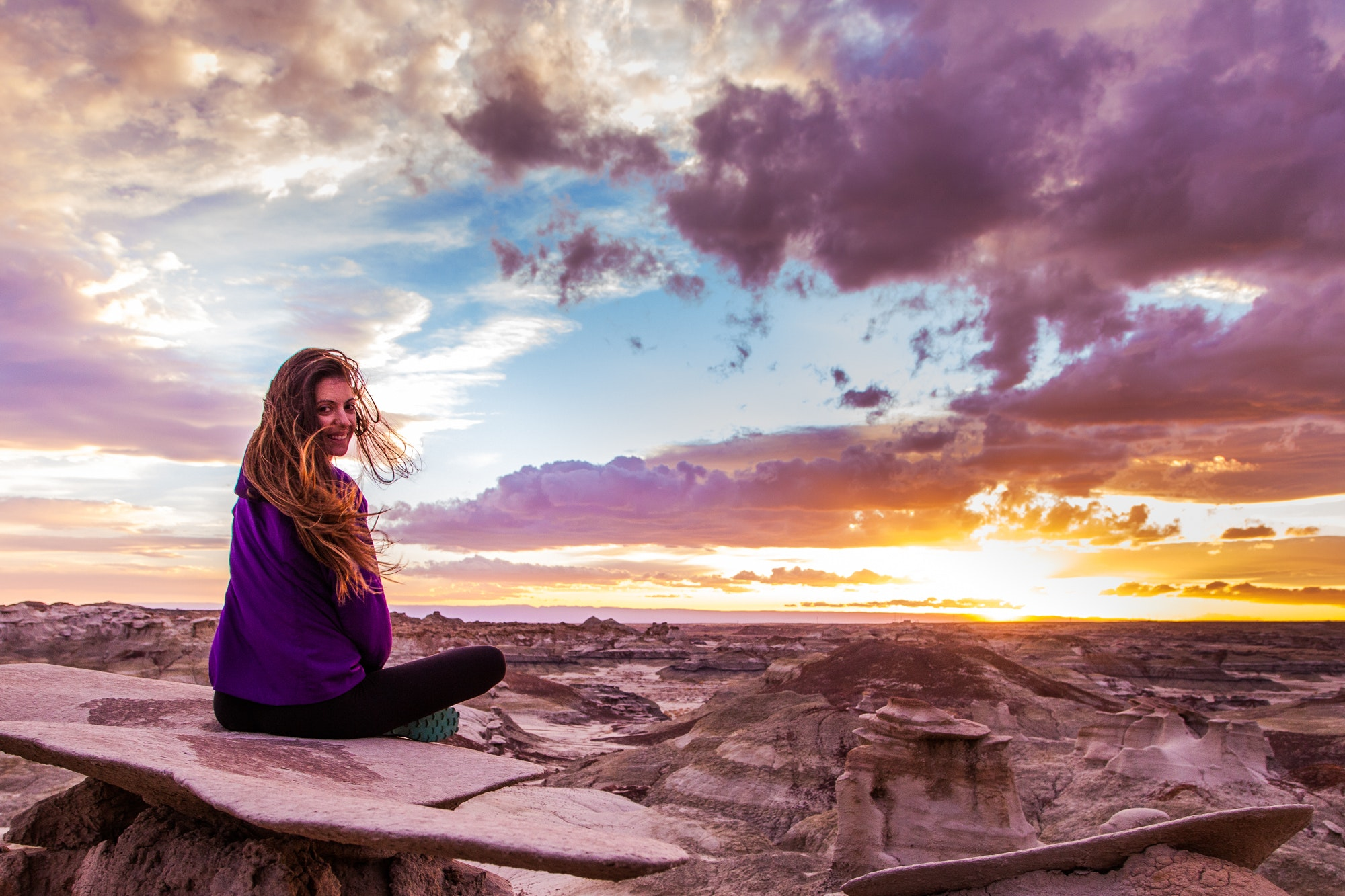 Woman sits on mountain under cloudy sky at sunset photo