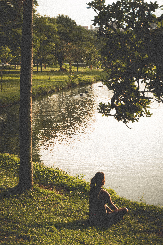 Woman sitting on grass by lake photo