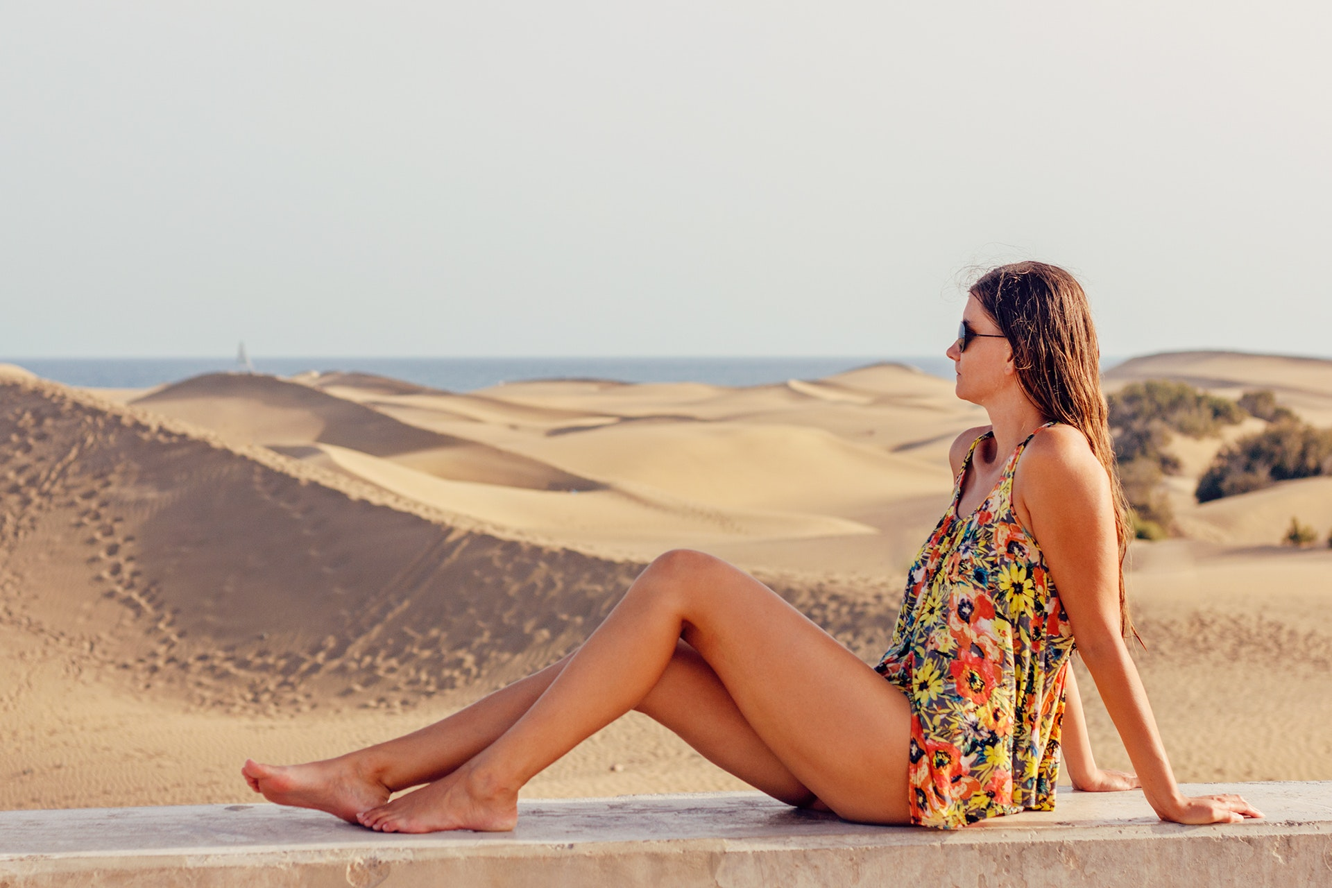 Woman sitting on sand at beach against sky photo