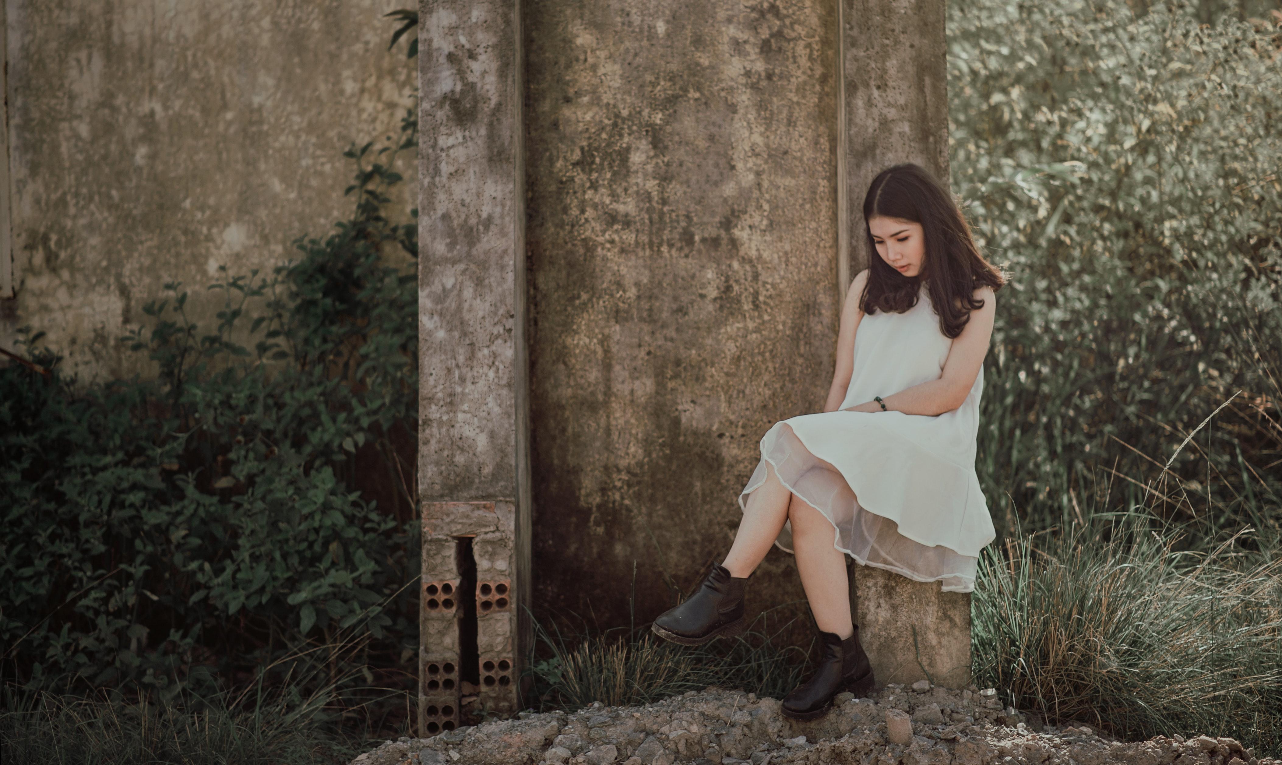 Woman sitting on slab near brown wall photo