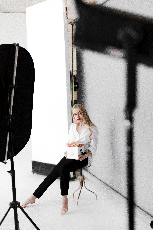 Woman sitting on stool while holding box photo