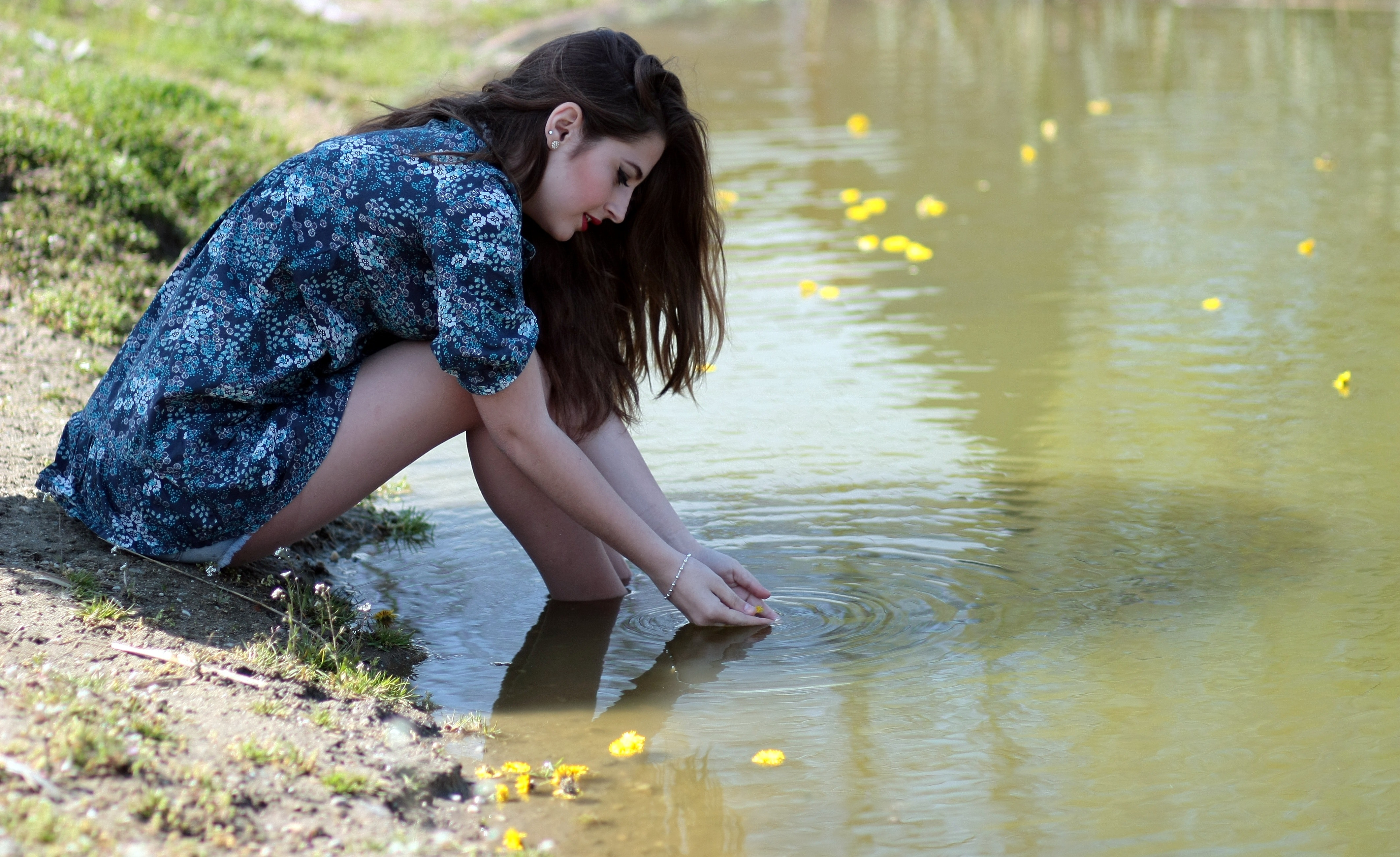 Woman soaking her feet on body of water during daytime photo