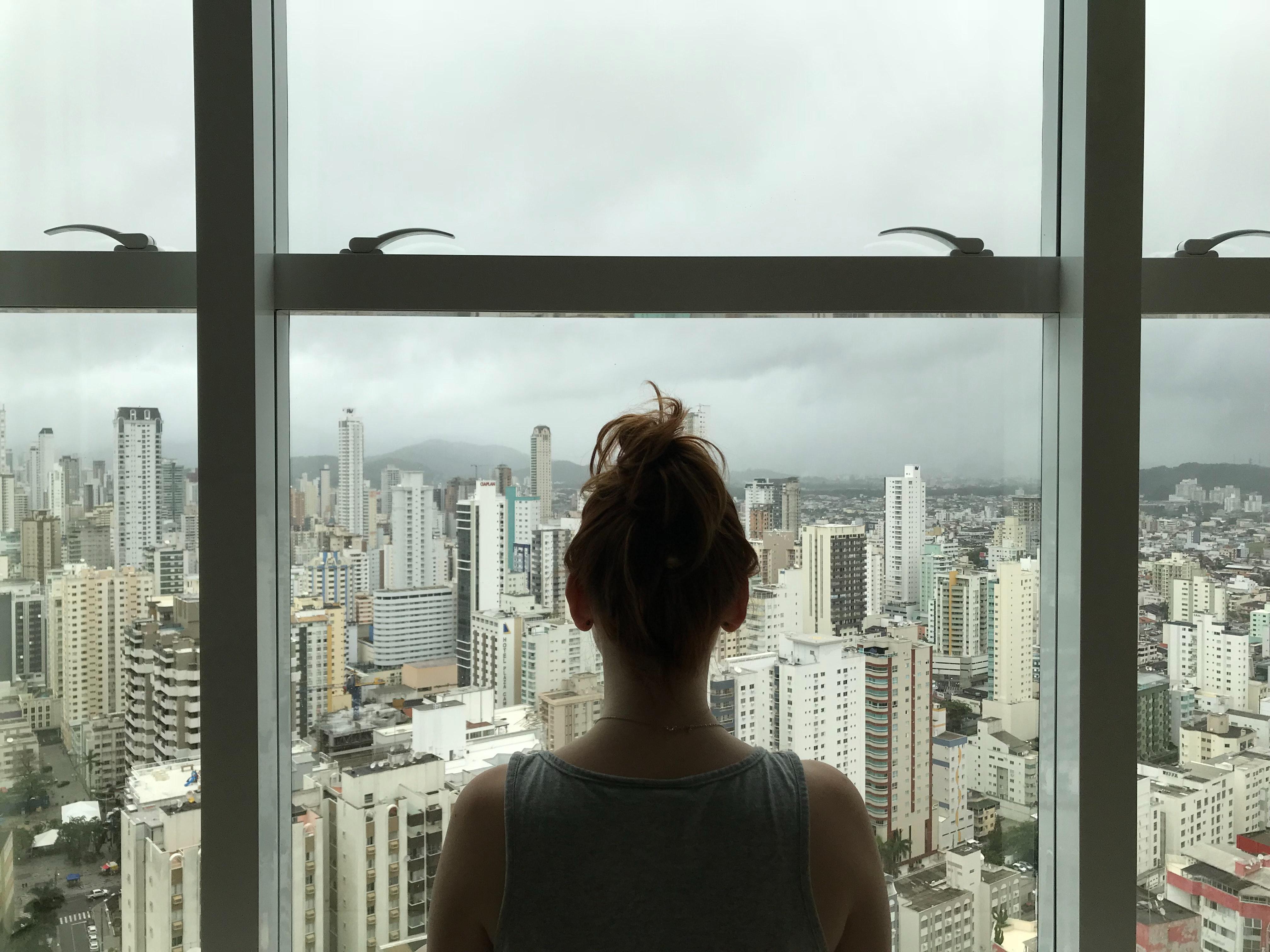 Woman standing near glass window photo