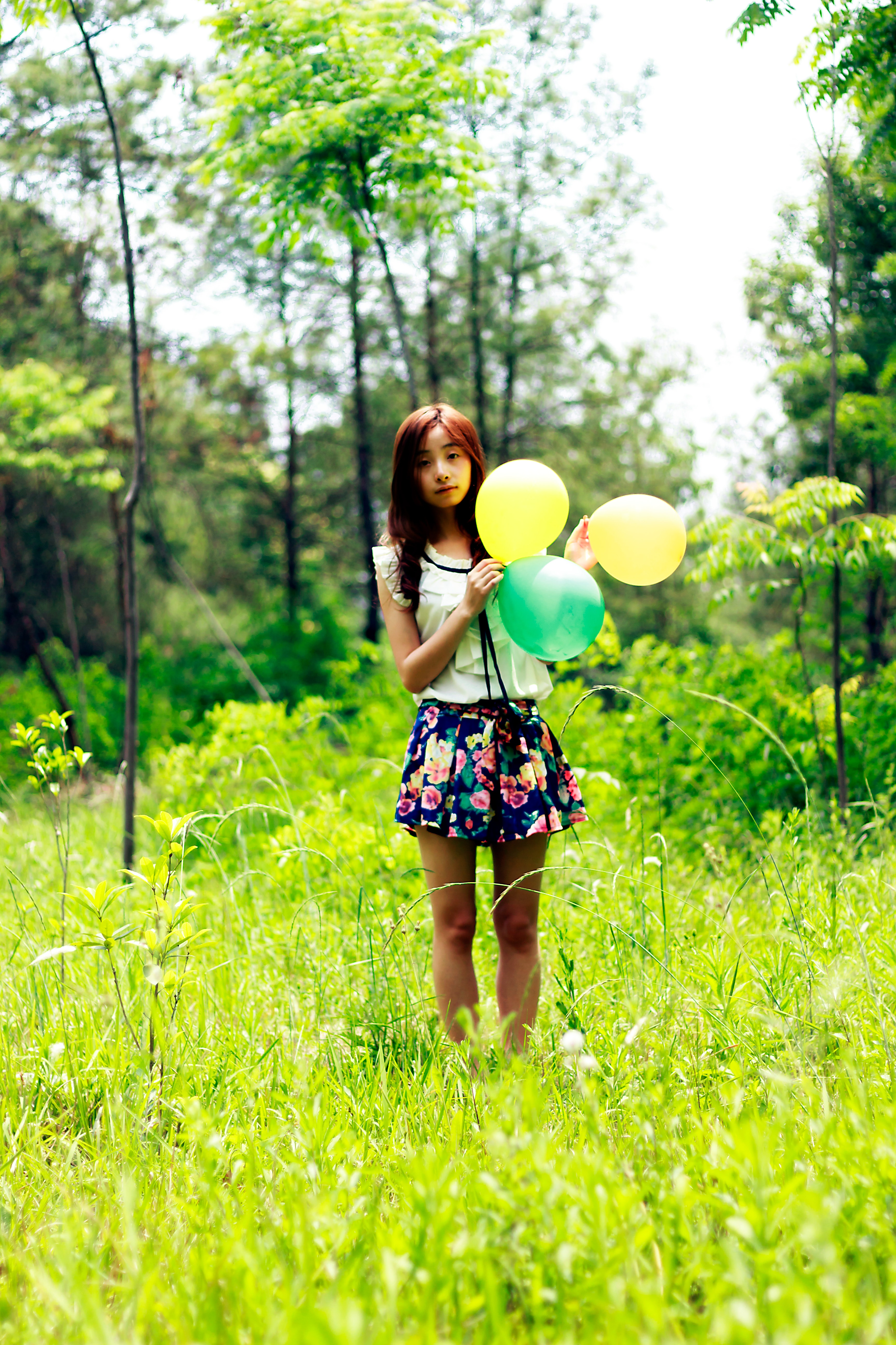 Woman standing on grass field while holding three balloons photo