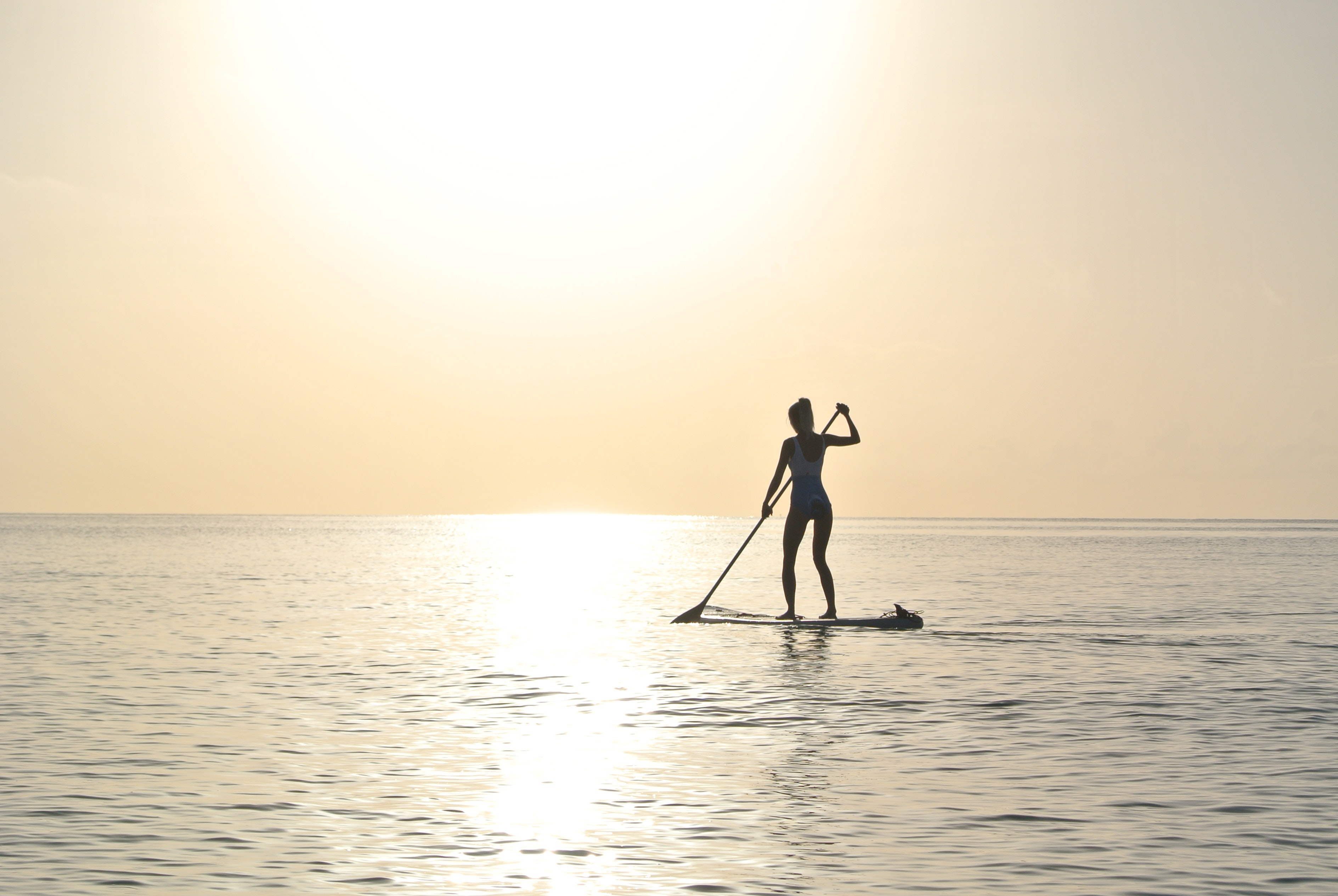Woman standing on paddleboard on body of water photo