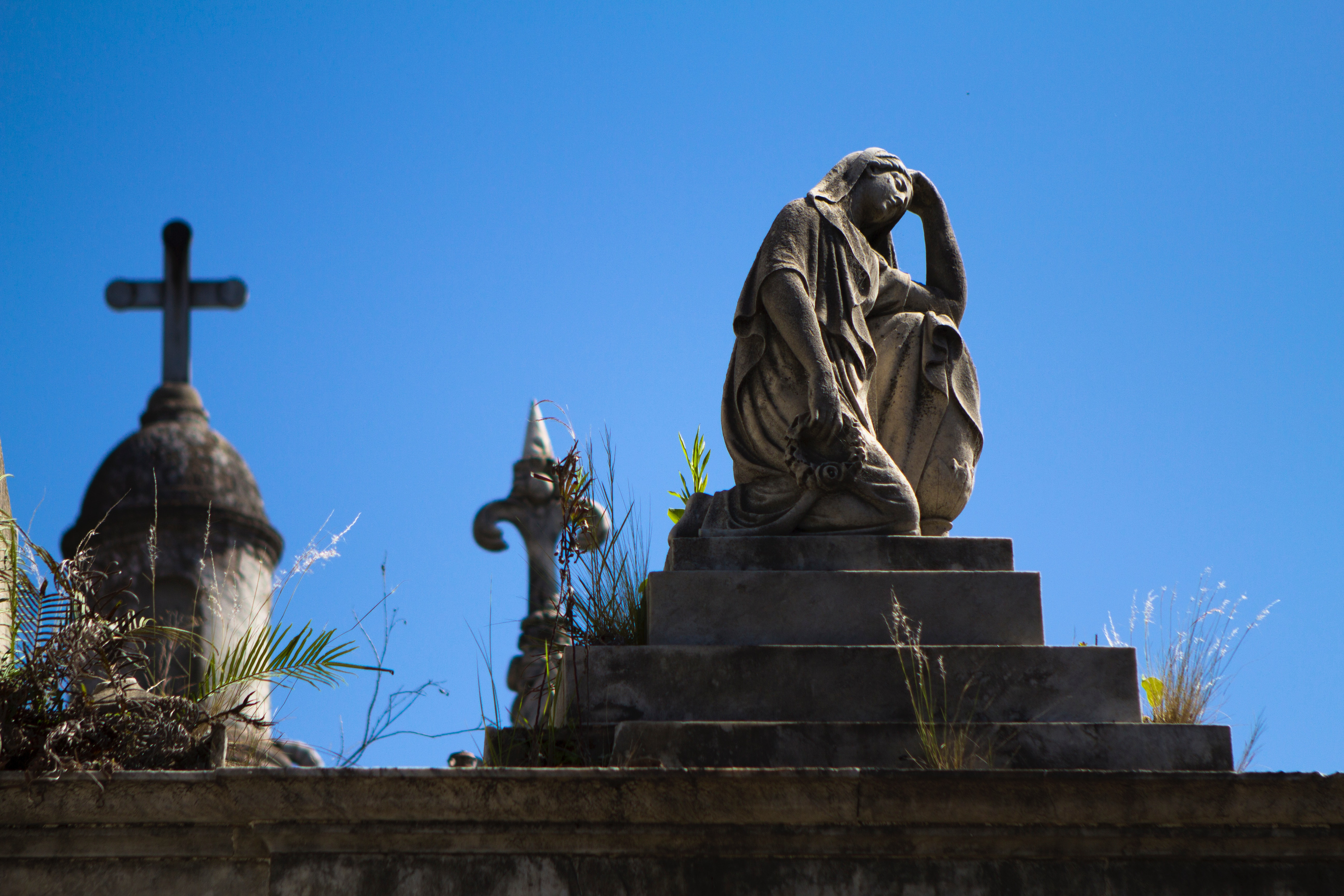 Woman statue near cross during daytime photo